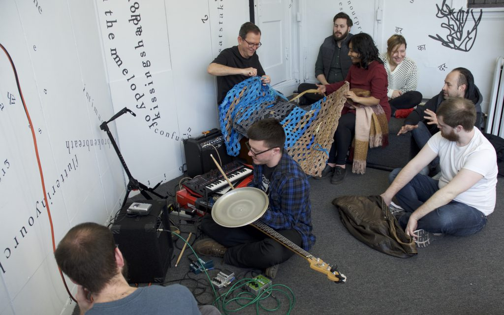 This photo is a medium-long shot, looking down toward several people sitting in a corner of the gallery. Jerry Bleem smiles while crocheting a large blue, grey, and tan piece. Udita holds the other end of it and smiles. In the foreground, a person sits holding an electric guitar, drum stick, and metal lid, with amplifiers and a keyboard nearby. Other people sit around and seem to speak to each other. Behind them are white walls and a white door onto which black vinyl letters are directly installed, in the form of words and phrases in English and Hindi. Text appears in different sizes and spatial orientations (e.g., right-side up, upside-down, diagonal, vertical, and organic shapes), with some words/phrases expanded in space, condensed, or intersecting with other text. A gestural drawing — also made of black vinyl — is shown near the center of the image.