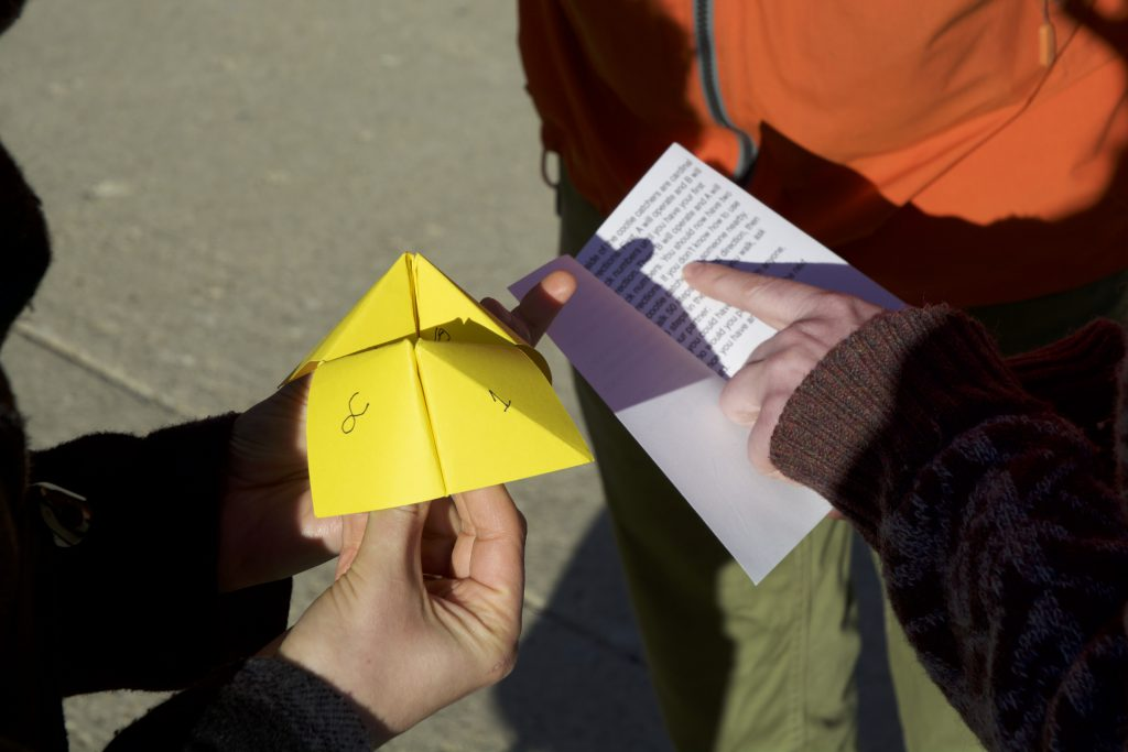 An extreme close-up of three people outside, using a cootie catcher. At left, a pair of hands holds a yellow cootie catcher. At right, another person holds a small booklet and points to its typed content. A third person stands just beyond that.