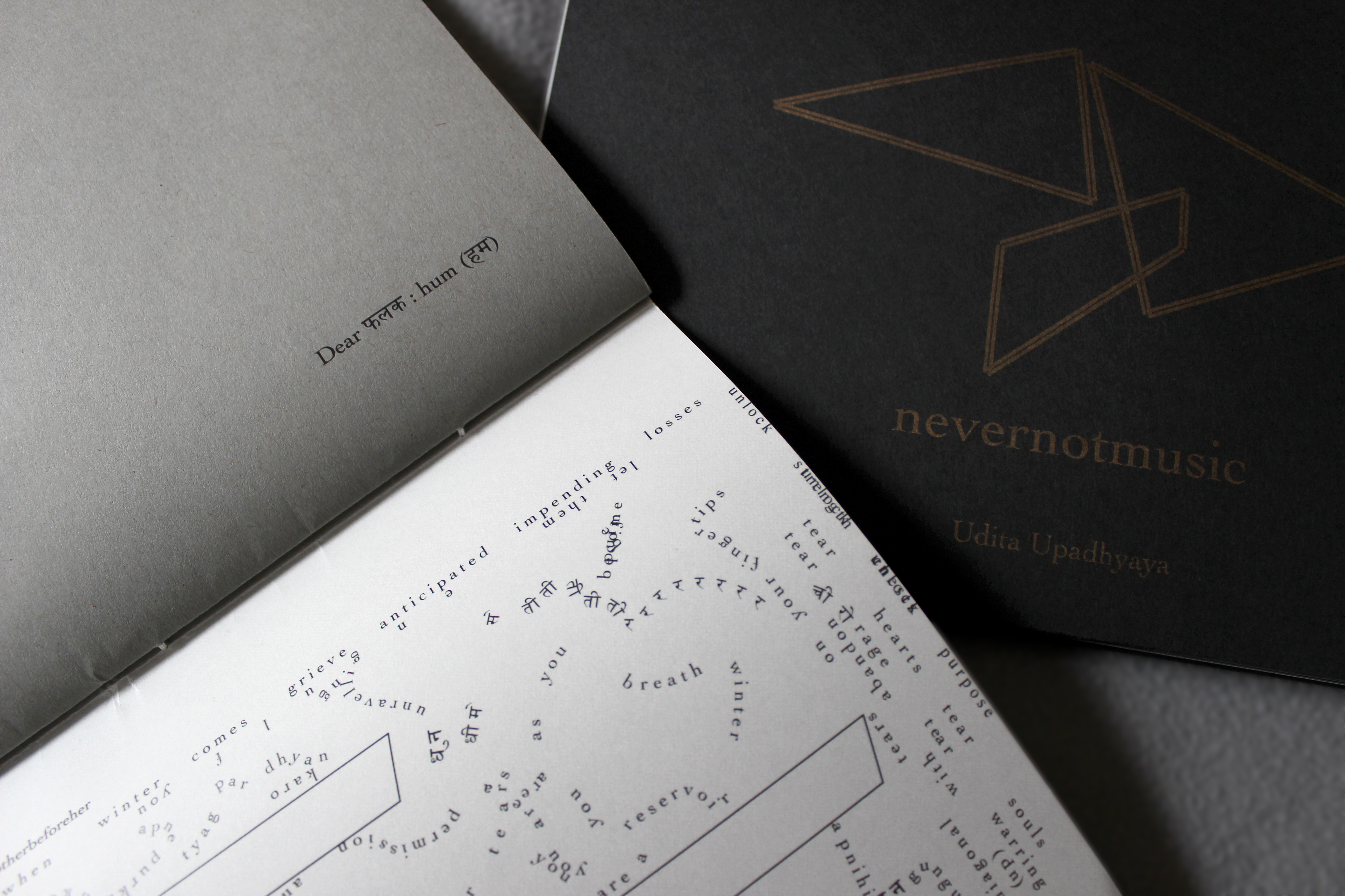 """This image depicts part of a performance score (bound into a thin book) and most of a cover (""""nevernotmusic"""" and """"Udita Upadhyaya"""" in gold text, with thin gold parallel lines forming two triangles and a rhombus, on black paper). On the top page (toward its bottom-right corner), it reads """"Dear फलक : hum (हम)"""" in black ink on grey paper. Across the binding, on the bottom page, are text in English and Hindi and hollow shapes (partially visible; possibly rhombuses), both in black ink against a whitish vellum background. Text appears in different sizes and spatial orientations (e.g., right-side up, upside-down, diagonal, vertical, and organic shapes), with some words/phrases expanded in space, condensed, or intersecting with other text. Along one side of the vellum page, text is flush with the edge; along the binding side, there is a white margin between the line of text and the binding."""