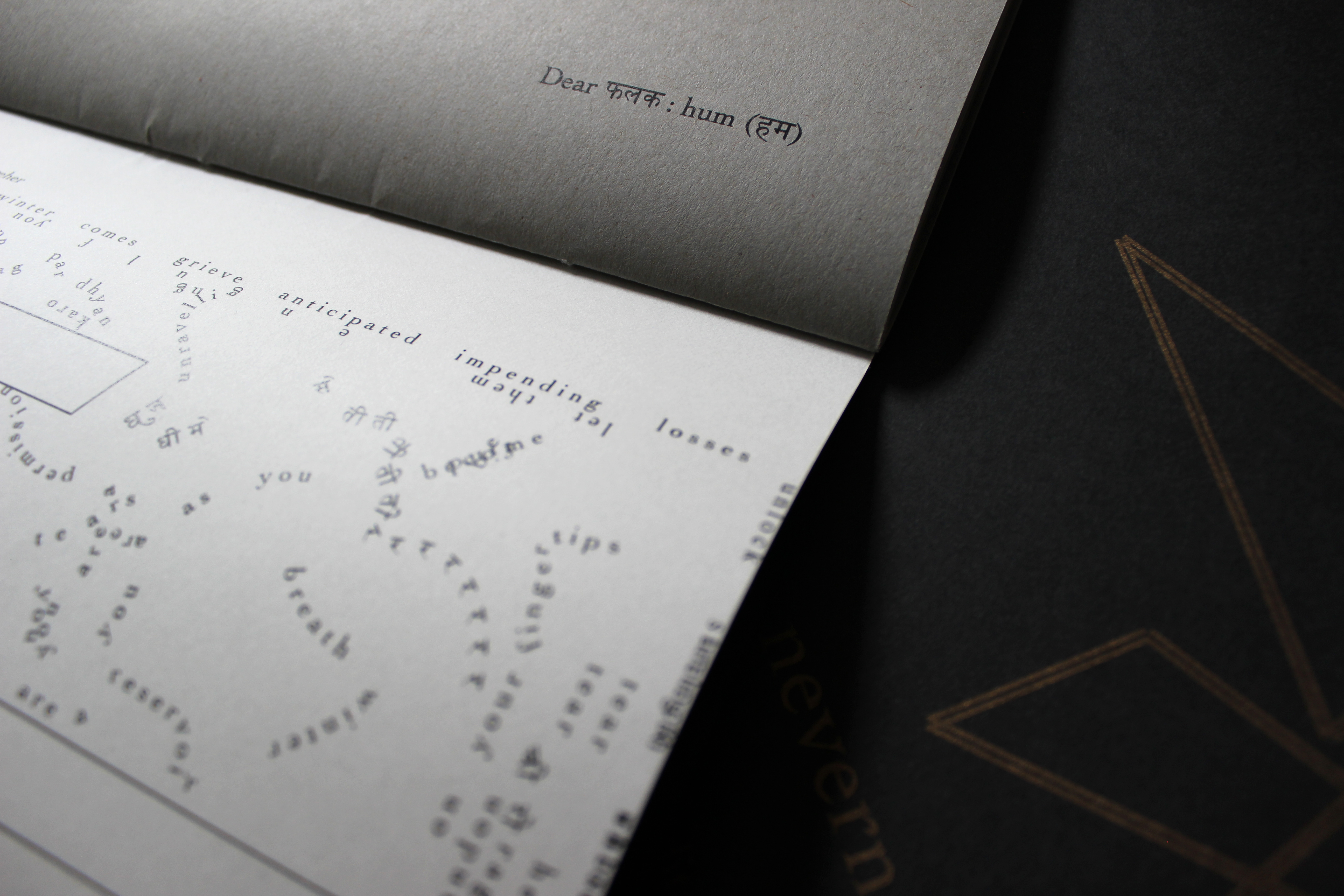 """This image depicts parts of a performance score (bound into a thin book) and of a cover (with the beginning of the title in gold and thin parallel gold lines forming triangles or rectangles, on black paper). On the top page (toward its bottom-right corner), it reads """"Dear फलक : hum (हम)"""" in black ink on grey paper. Across the binding, on the bottom page, are text in English and Hindi and hollow shapes (partially visible; possibly rhombuses), both in black ink against a whitish vellum background. Text appears in different sizes and spatial orientations (e.g., right-side up, upside-down, diagonal, vertical, and organic shapes), with some words/phrases expanded in space, condensed, or intersecting with other text. Along one side of the vellum page, text is flush with the edge; along the binding side, there is a white margin between the line of text and the binding."""