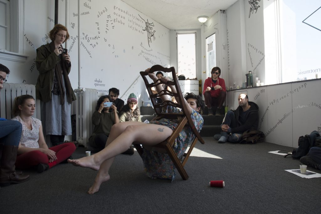This is a still of a performance. Tannaz is in the middle of the gallery floor. Tannaz's body is suspended through the inside of a chairframe—which leans forward at a roughly 60-degree angle—with the toes of Tannaz's right foot touching the floor and Tannaz's left leg kicked into the air. Tannaz's hips rest on the edge of the seat's frame and Tannaz's torso cuts through the seatless seat area. From behind the chair (facing it), Tannaz reaches up to grip the back of the chair. Red thread is visible around the chair leg and a spool of red thread is in on the floor near Tannaz. In the background, Udita and audience members sit and watch. Words, phrases, and shapes on the gallery wall and windows are visible behind them.
