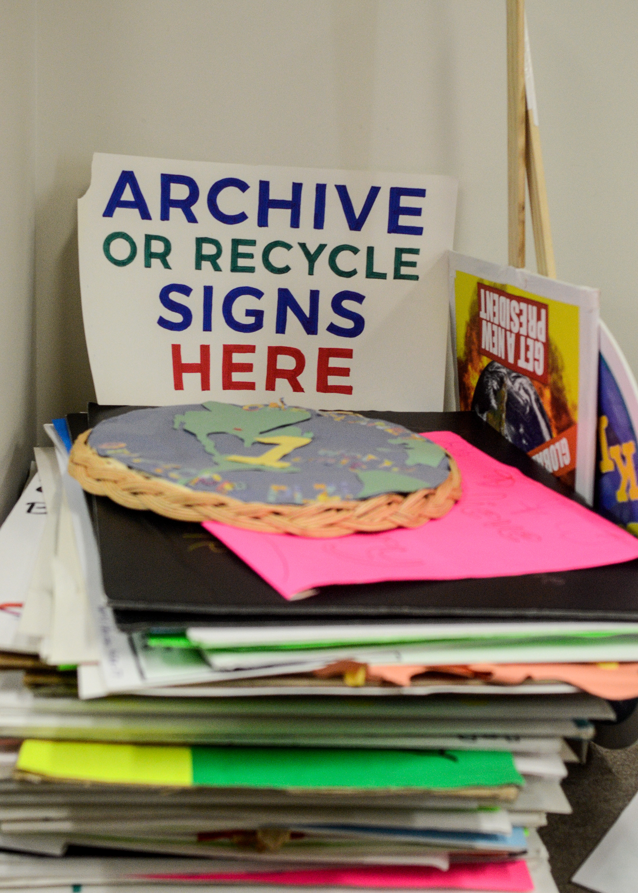 """Image: A stack of multicolored poster board signs is shown. A sign that reads """"Archive or Recycle Signs Here"""" stands above the stack. One sign is the map of the world pasted onto a woven basket. Two signs with sticks attached can be seen to the right. Image by William Camargo."""