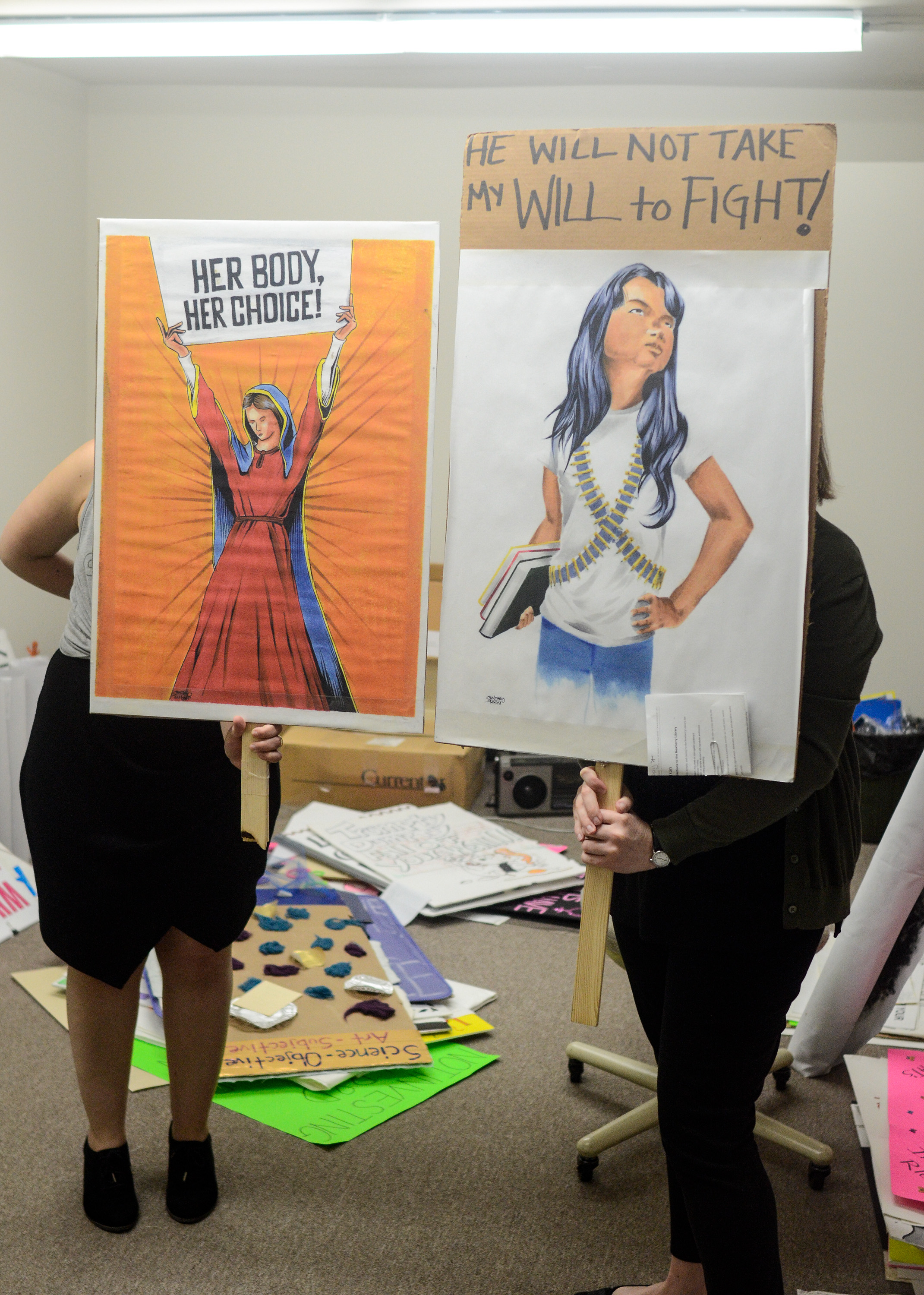 """Image: Catherine Grandgeorge and Jennifer Patiño Cervantes hold up signs in front of them. The two signs are of images made by and donated by artists Adrian Santiago-Alvarez. One shows a Virgin Mary like figure holding a sign that says """"Her Body Her Choice."""" The other shows a defiant young woman holding books and wearing bandoliers under a sign that says """"He Will Not Take My Will to Fight!"""" Image by William Camargo."""