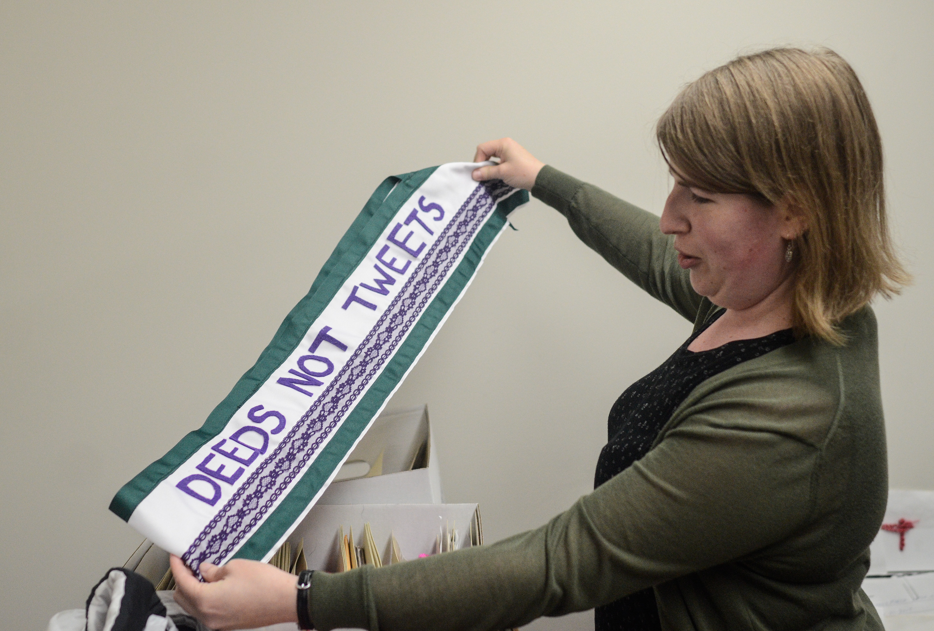 """Image: Catherine Grandgeorge holds up a green, white, and purple sash that says """"Deeds Not Tweets"""" with both arms. Image by William Camargo."""