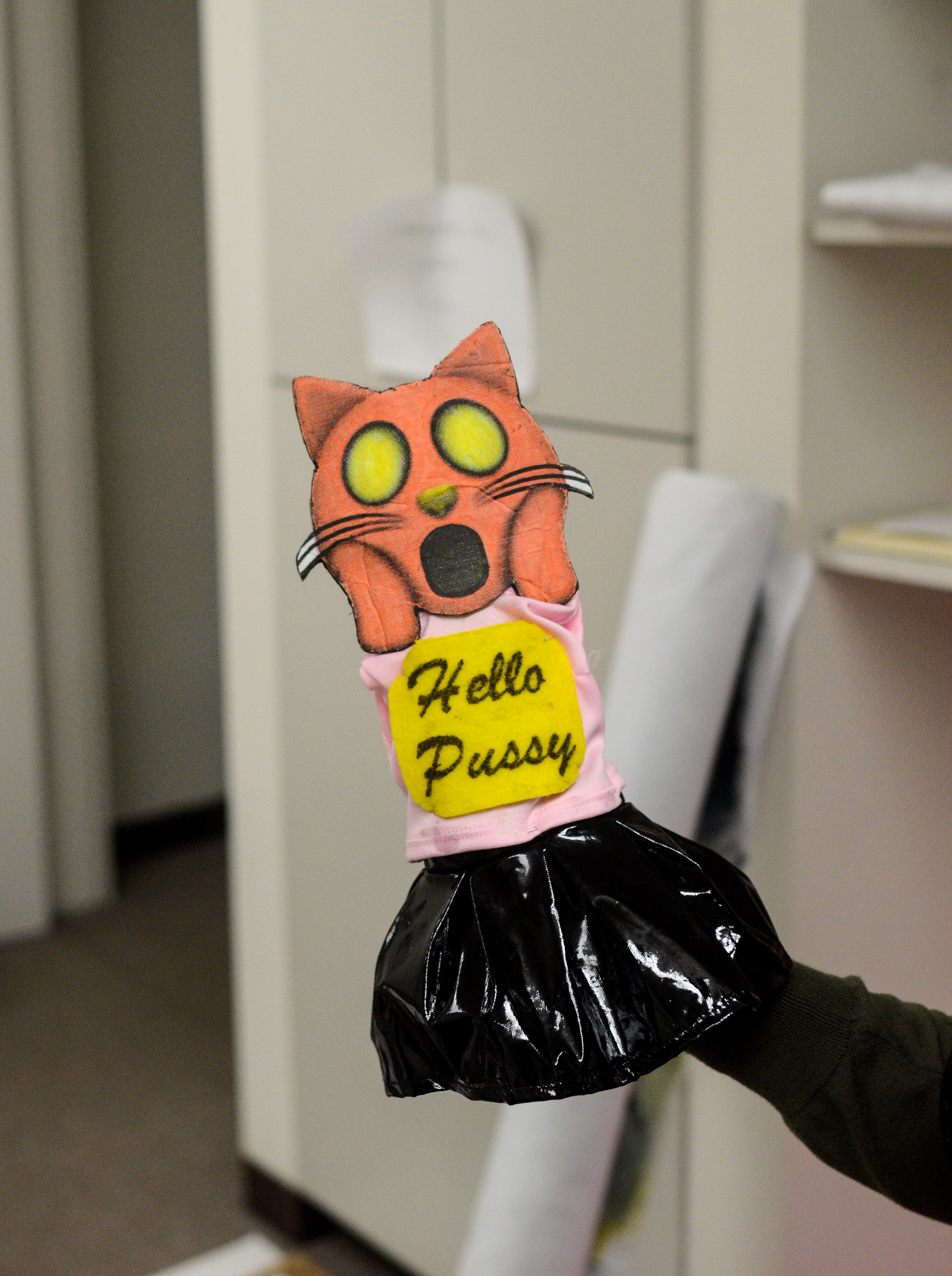 """Image: A hand puppet has the head of an orange emoji cat making a shocked face that alludes to """"The Scream"""" by Edvard Munch. It wears a pink and black outfit with a yellow sign that says """"Hello Pussy."""" Image by William Camargo."""