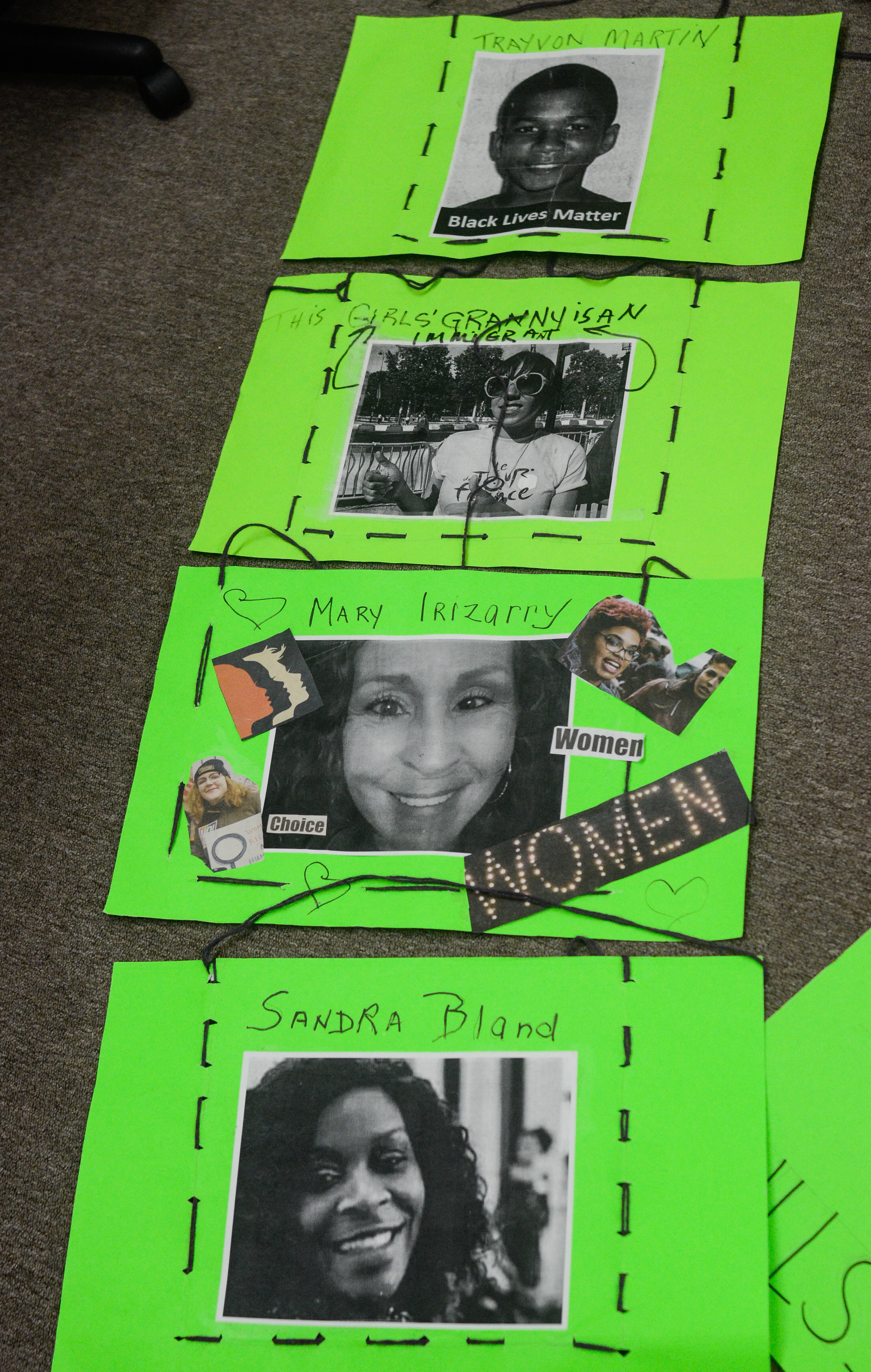 """Image: Four green poster boards are stitched together with black thread. It appears designed to be draped across the front and back of the body. Photos are accompanied with text on each sign. From top to bottom, the text reads """"Trayvon Martin,"""" """"This Girls' Granny is an Immigrant,"""" """"Mary Irizarry,"""" along with """"Women"""" and """"Choice,"""" and lastly """"Sandra Bland."""" Image by William Camargo."""
