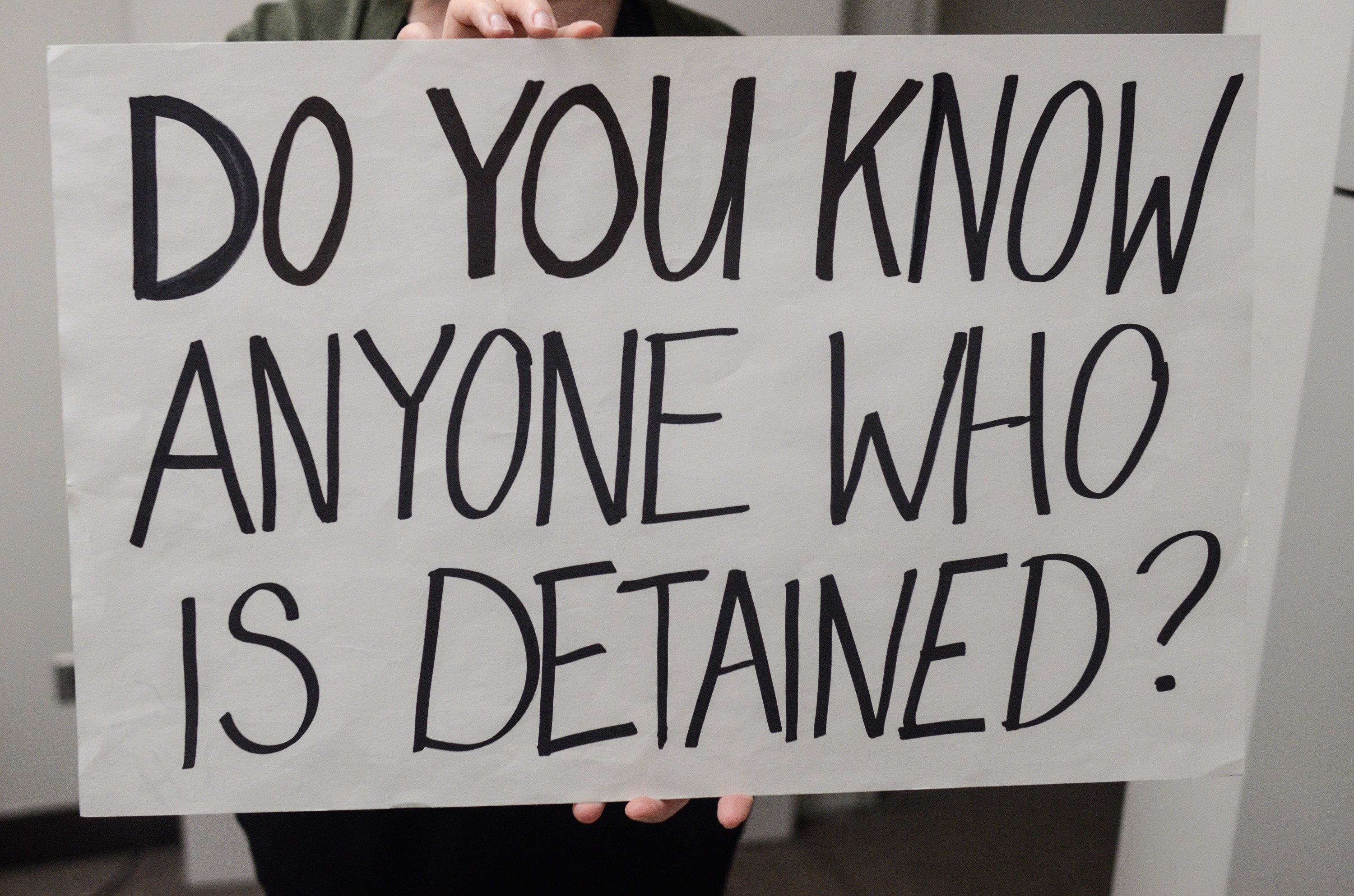 """Image: Catherine Grandgeorge holds up a white sign with black lettering that reads """"Do You Know Anyone Who Is Detained?"""" that was used at airports by lawyers responding to the travel ban. Image by William Camargo."""