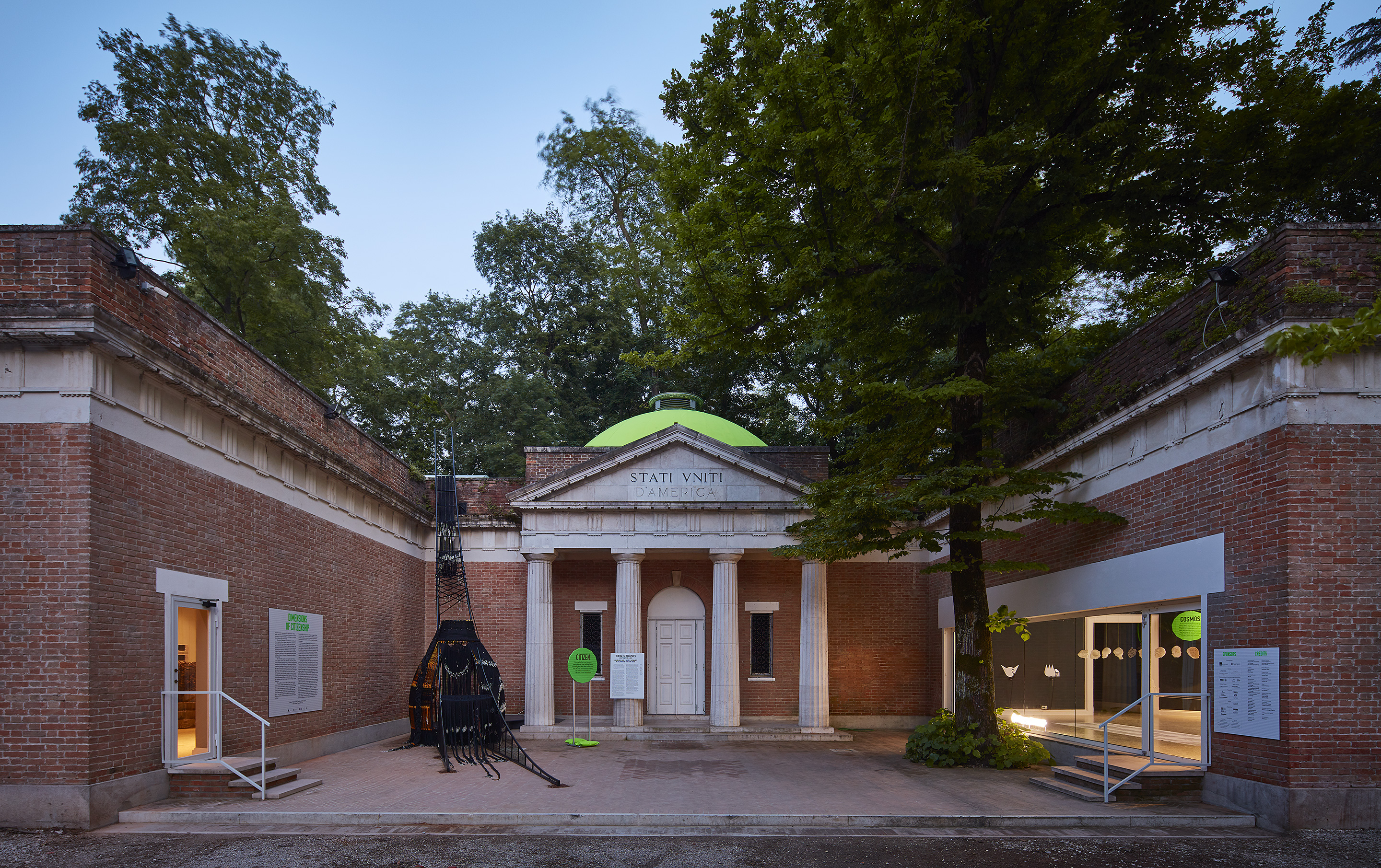 Image: The 2018 U.S. Pavilion. The image shows an exterior view of the U.S. Pavilion at dusk with light glowing from the windows of the gallery spaces. Photo © Tom Harris. Courtesy of the School of the Art Institute of Chicago and the University of Chicago.