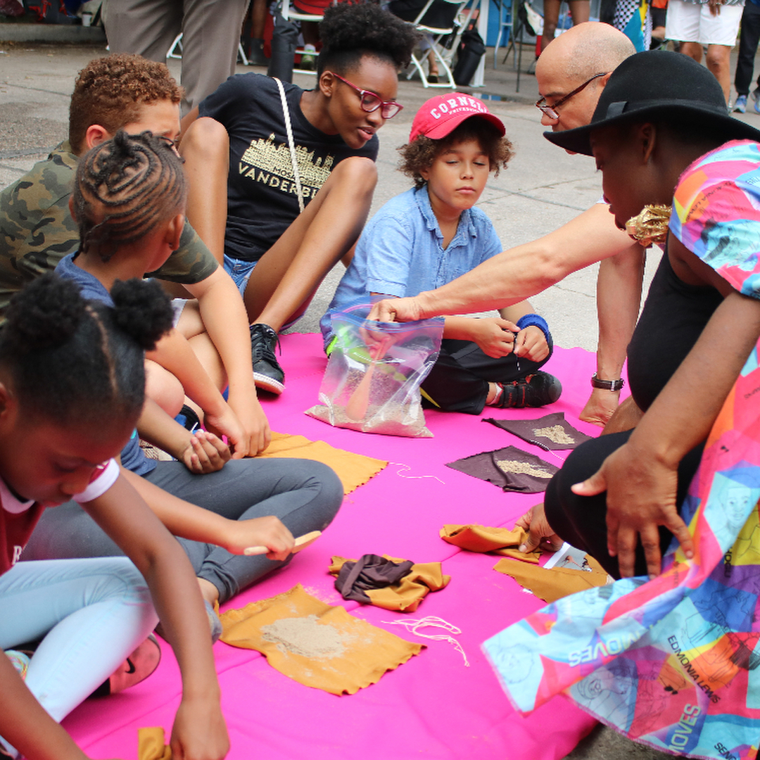 Image: Wisdom Baty (right) wears a brightly colored cape and shows a group of children how to fill nylon materials with sand at Back Alley Jazz. Image courtesy of the Museum of Vernacular Arts.