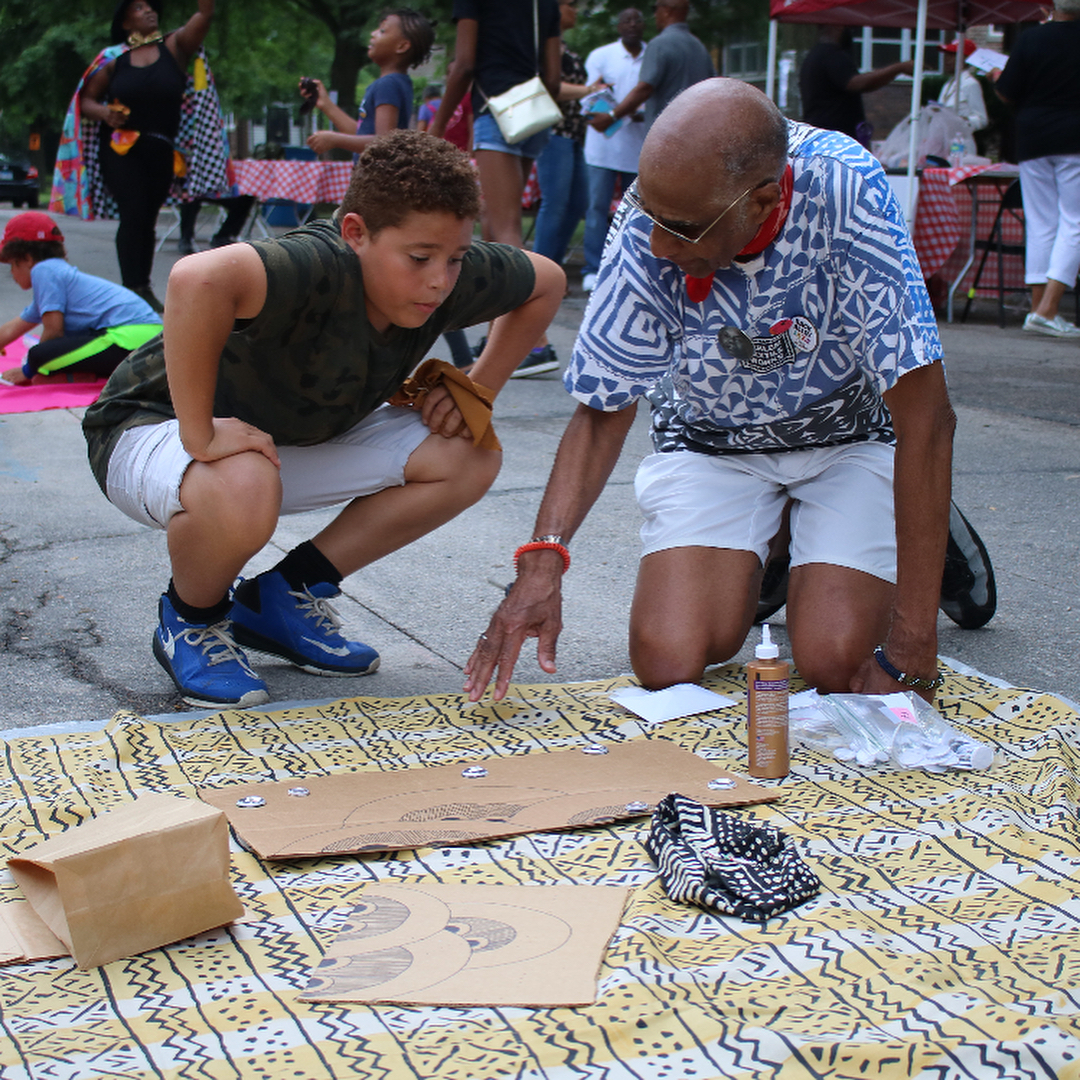 Image: A 9- or 10-year-old child with curly dark hair squats beside Robert Earl Paige as the artist gestures towards a design created on cardboard and lying flat on a textile on the concrete. Image courtesy of the Museum of Vernacular Arts.