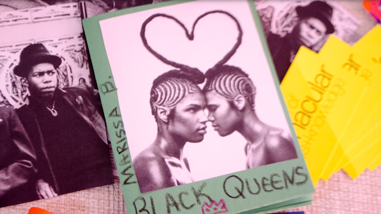 "A zine entitled ""Black Queens"" by Marissa B. On the cover, two young black people with bare shoulders and intricately braided hair stand forehead-to-forehead. A single braid of hair extends from each of their heads, curving forward to form a heart between them. Photo by Jordan Paige. Image courtesy of the Museum of Vernacular Arts."