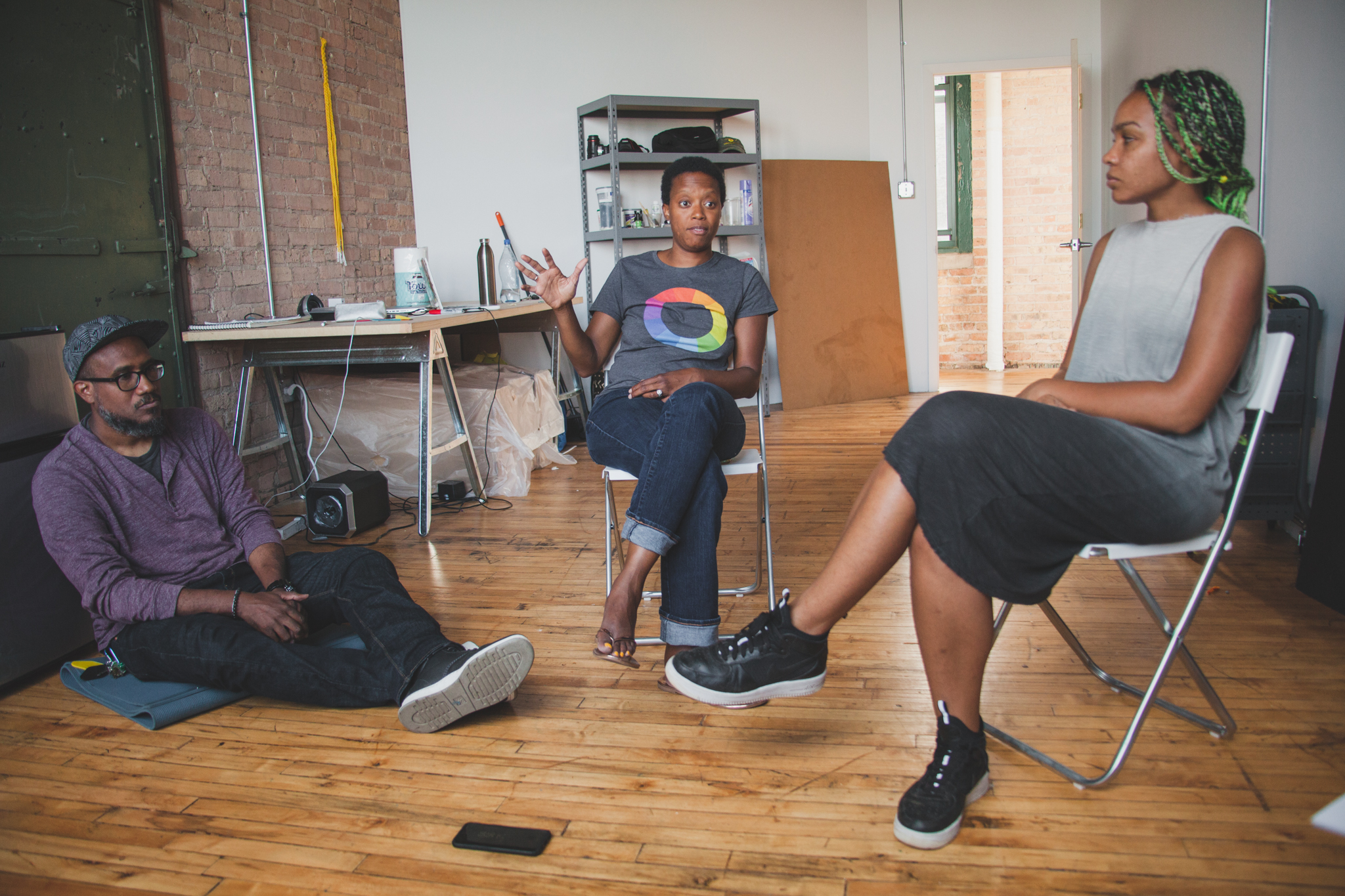 Image: Andres, Amanda, and Shani in a studio at Bridgeport Art Center, 2018. The image shows Andres sitting on the ground, Amanda and Shani sitting in chairs near him and Amanda is speaking as the other two listen. Photo by Ally Almore.