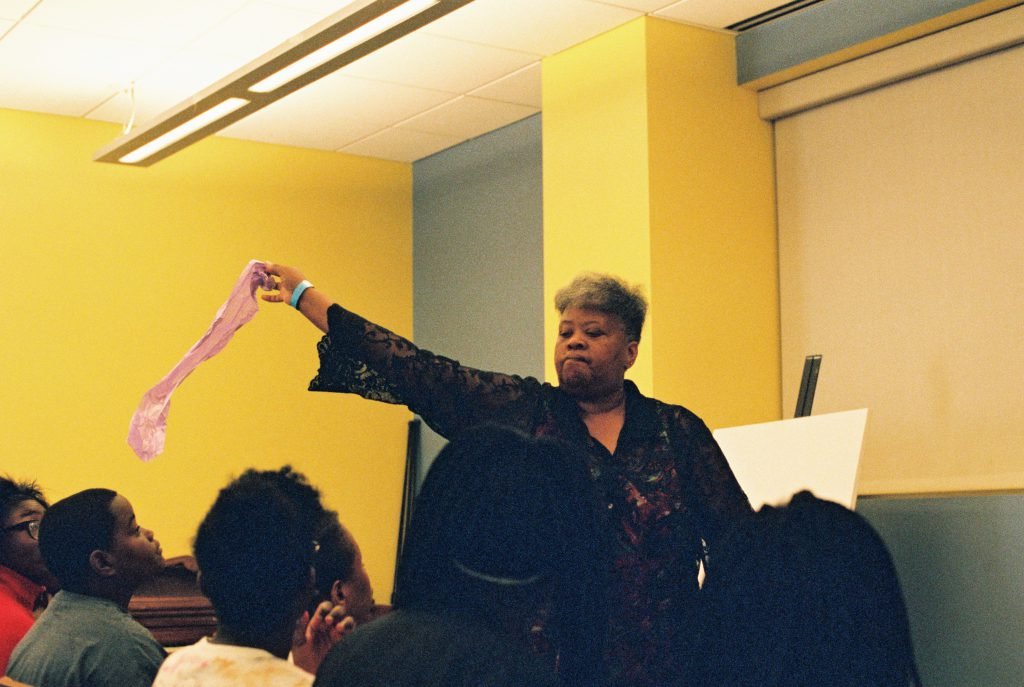 Image: A BBF Family Services teaching artist performs in front of middle school-aged children, waving a lavender ribbon over her rapt audience. Photo by Eric K. Roberts.