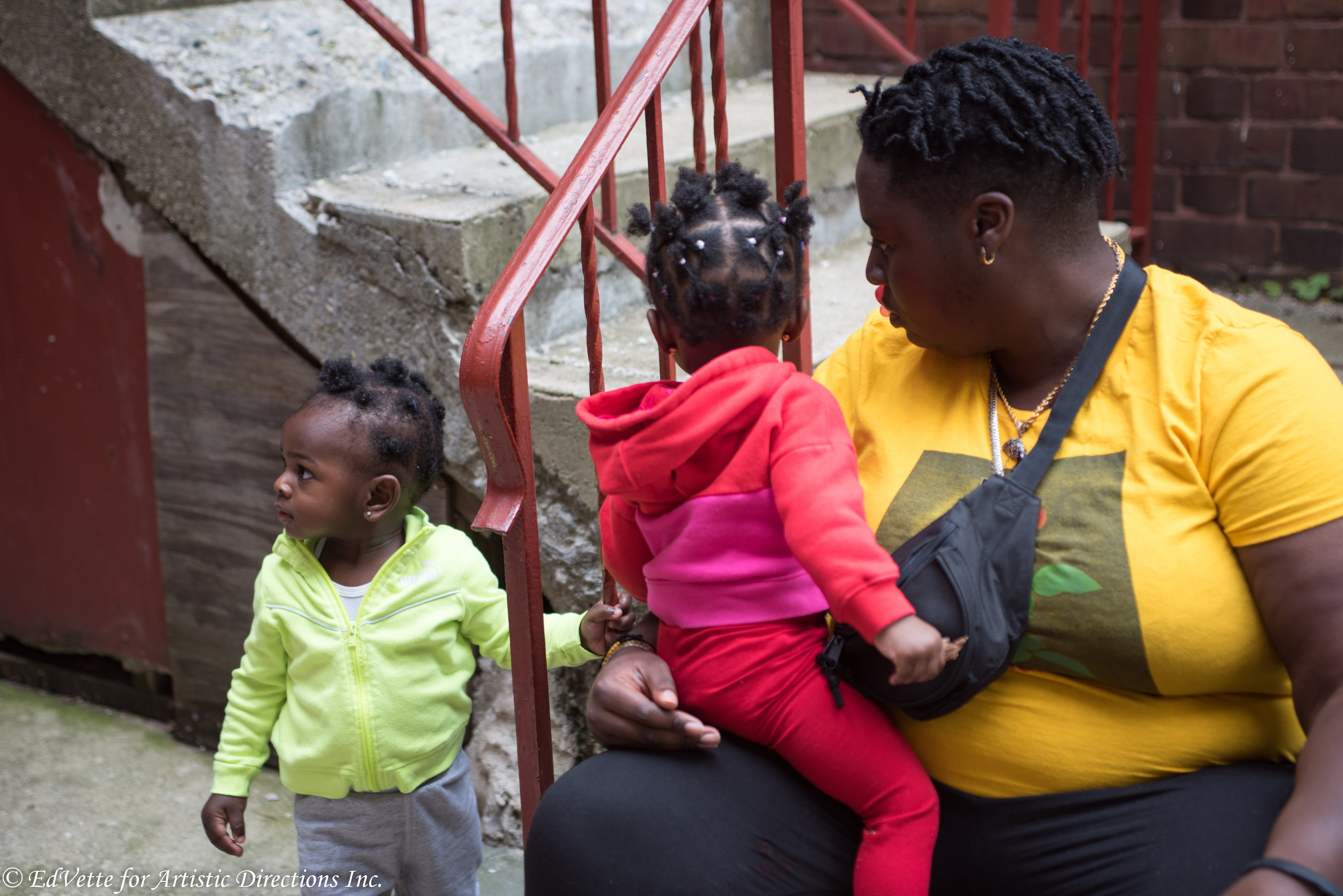 IMAGE: AnnMarie Brown sits on a stairwell outside of United Church of Rogers Park with a child seated on her lap and another standing a short distance away.