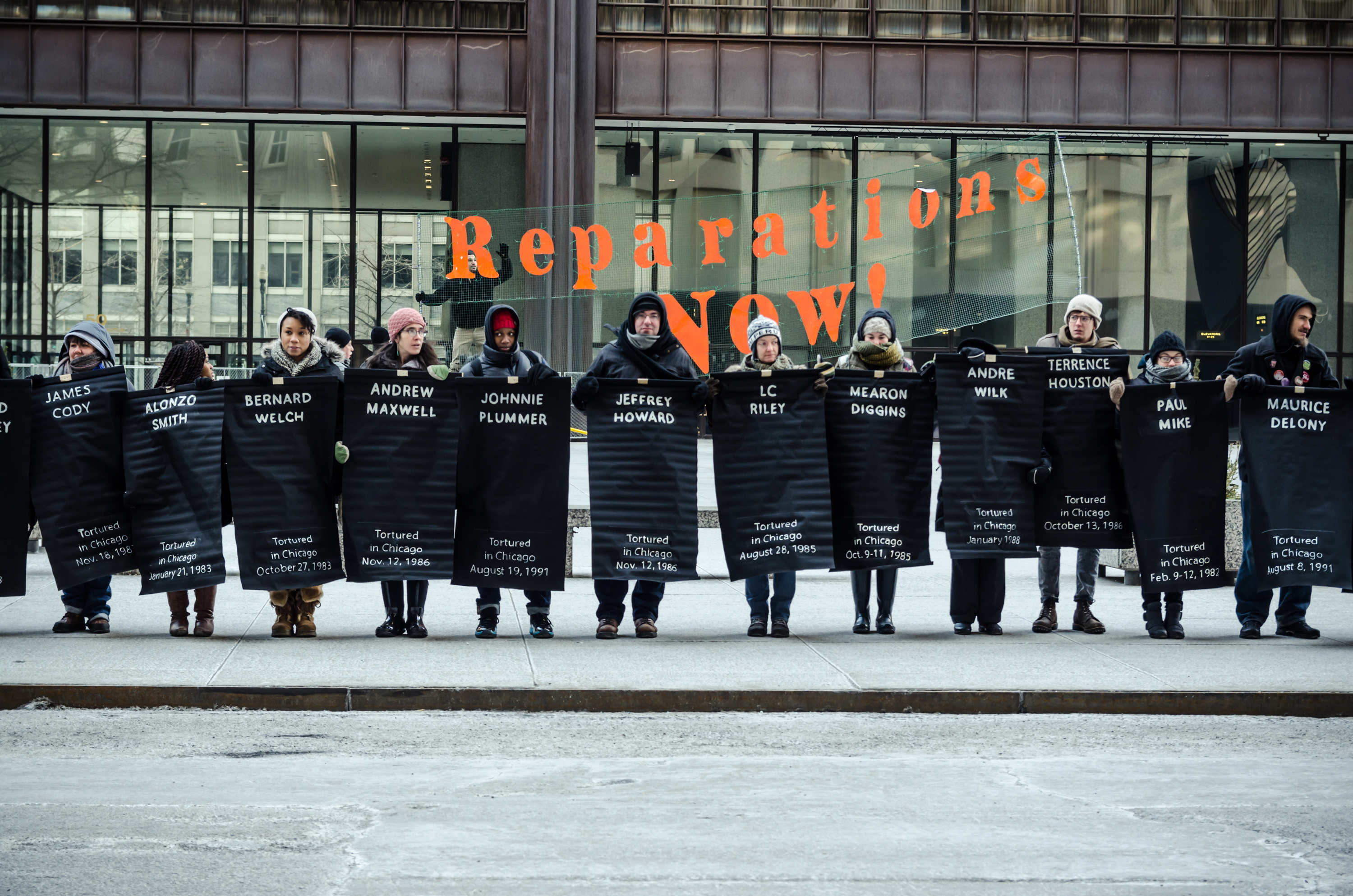 "Image: People lined up facing the camera. They are holding up Black posters with the names of victims of torture by Chicago Police inscribed in white. Behind them is a transparent banner with the words ""Reparations NOW!"" inscribed in orange. Photo taken February 2015 at the Rally for Reparations organized by The Chicago Torture-Justice Memorials, Project NIA, Amnesty International USA, and We Charge Genocide. Photo courtesy of the artist."