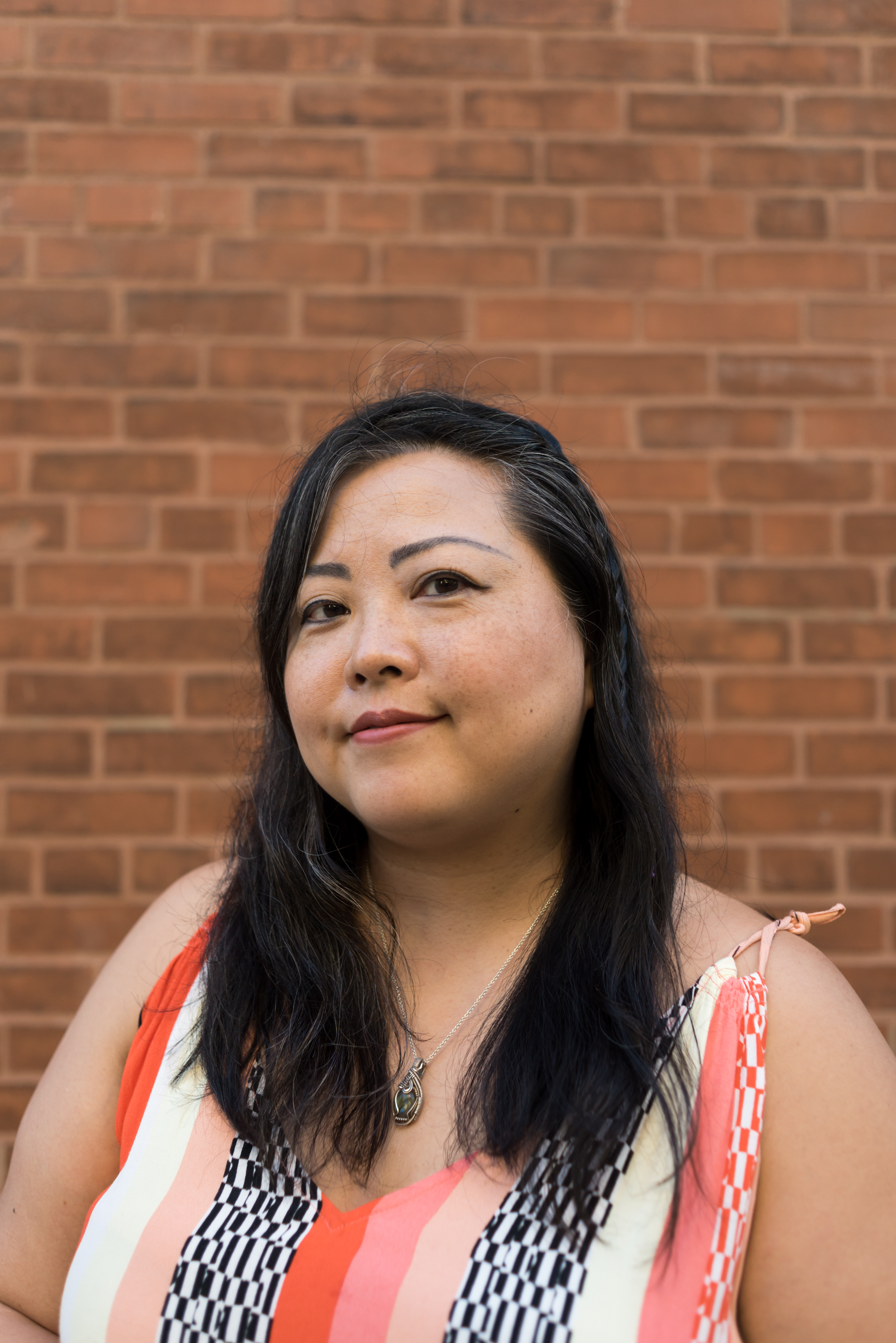 Image: A portrait of the artist Sarah-Ji standing in front of a brick wall wearing a patterned dress. She looks directly at the camera with a slight smile. Portrait taken by Ireashia Bennett.