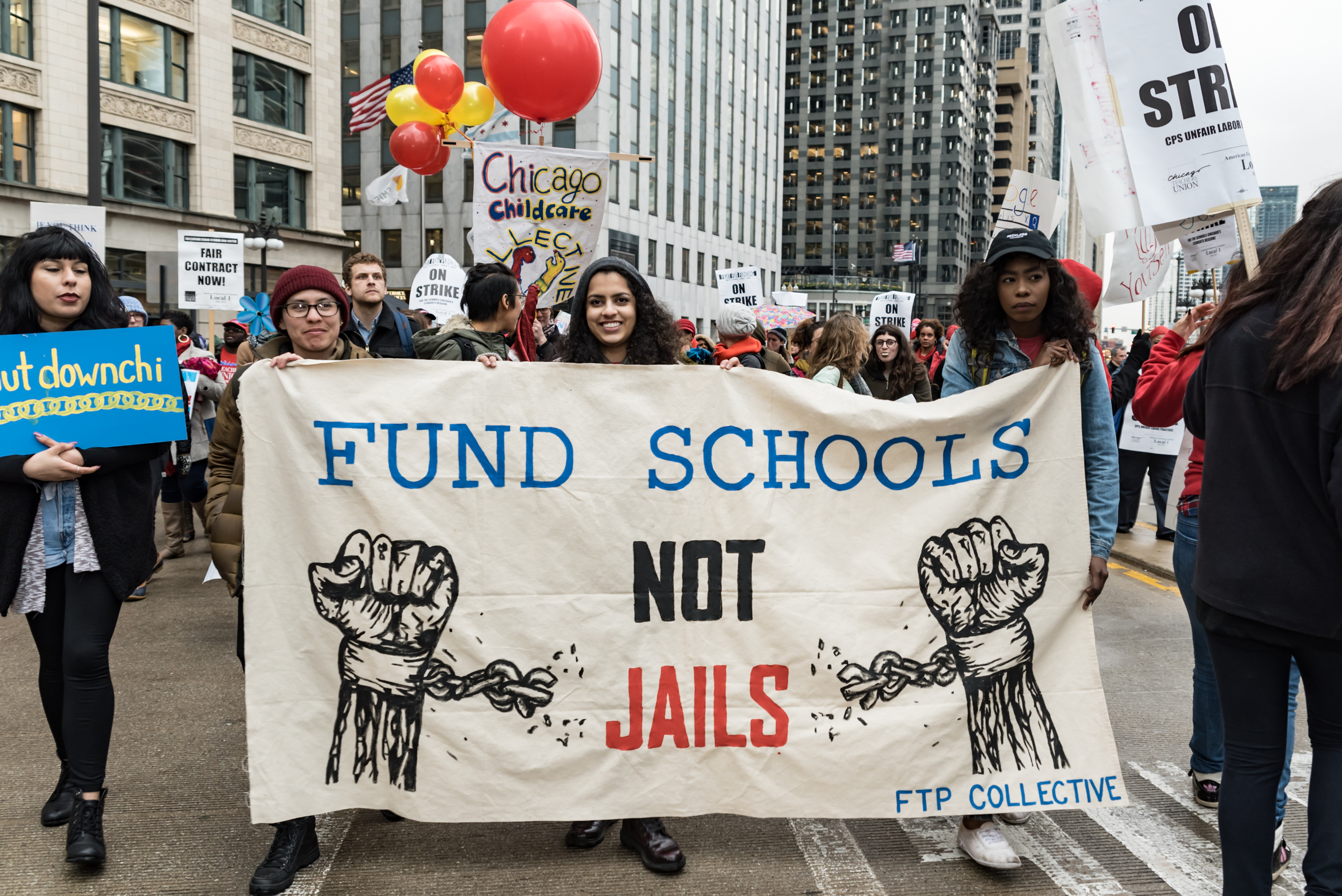 "Image: Photo of a group of people rallying in downtown Chicago. In the center of the image are three people of color holding up a sign which says: ""Fund Schools Not Jails"" in the center. On either side of the words are images of painted fists with broken shackles around the wrists. On the bottom right of the poster is ""FTP Collective."" Photo taken April 2016 at the Shut Down the Chi Rally. Photo courtesy of the artist."