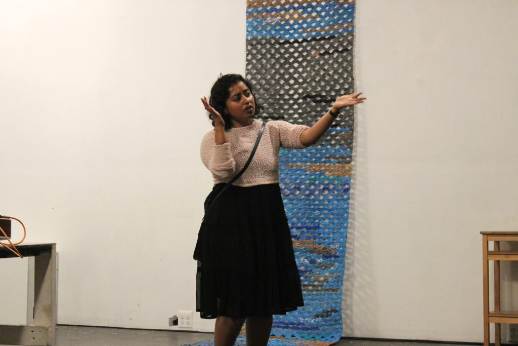 "Image: Udita Upadhyaya at the ""nevernotmusic"" book release at TriTriangle. The artist stands at the center of the image, gesturing with both arms while speaking. Hanging on the wall behind Udita and extending onto the floor is a blue, grey, brown, and black artwork by Jerry Bleem, which was crocheted as part of a performance in response to Udita's score, ""Dear Jerry and Nick: Hold (a hand a spine a heart a whole self)."" Udita wears a light-colored, textured sweater and black skirt. Photo by Caleb Neubauer."