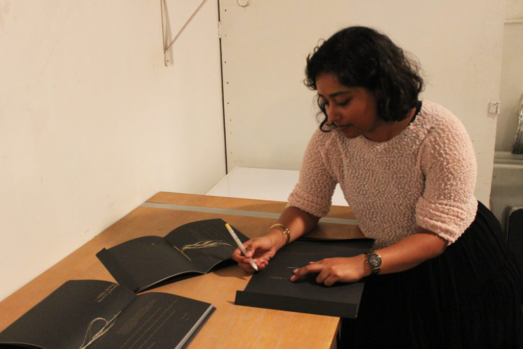"Image: Udita Upadhyaya at the book release for ""nevernotmusic."" The artist leans over a table, looking down as she writes in gold pen inside a copy of her book. Next to Udita are two other copies, open to their centerfolds, where gold thread is visible. The artist wears a light-colored, textured sweater and black skirt. Photo by Caleb Neubauer."
