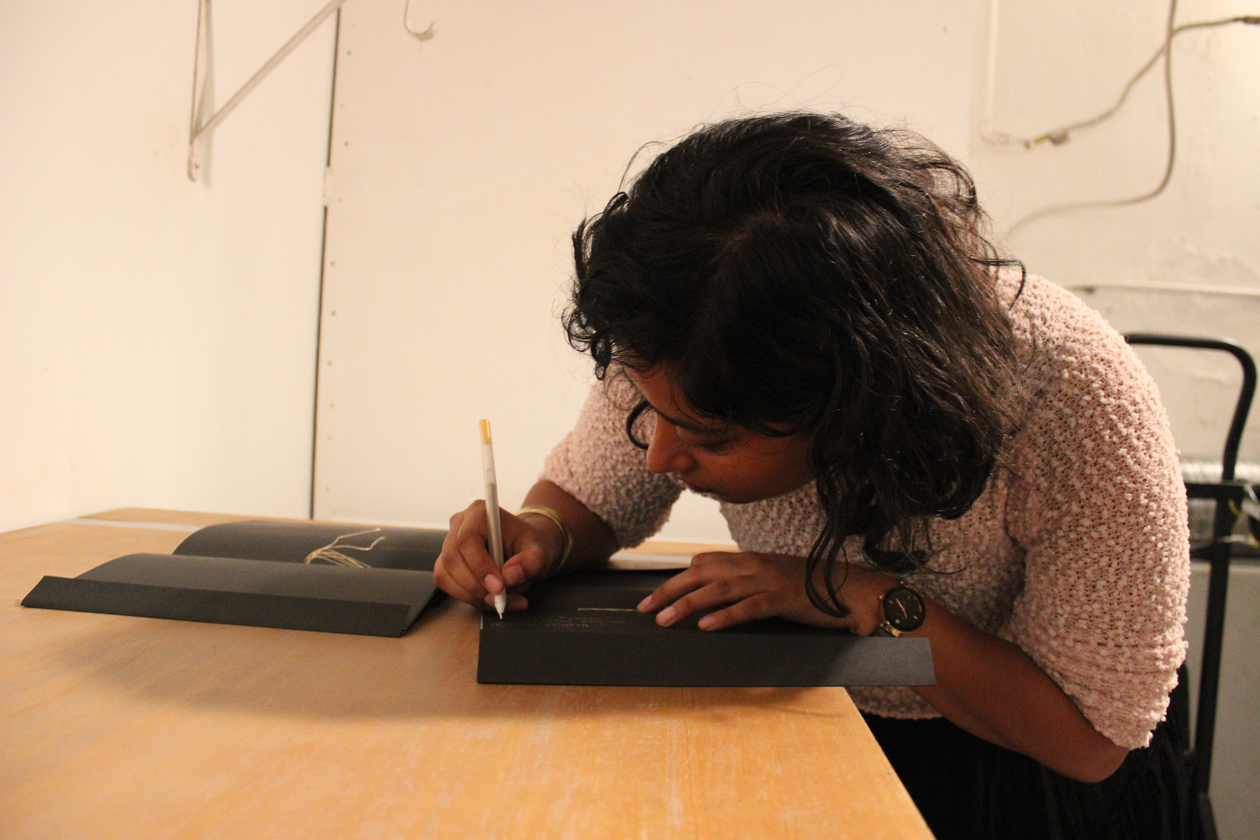 "Featured image: Udita Upadhyaya at the book release for ""nevernotmusic,"" at TriTriangle. The artist leans over a table, looking down as she writes in gold pen inside a copy of her book. Next to her is another copy, open to its centerfold, where gold thread is visible. The artist wears a light-colored, textured sweater. Photo by Caleb Neubauer."
