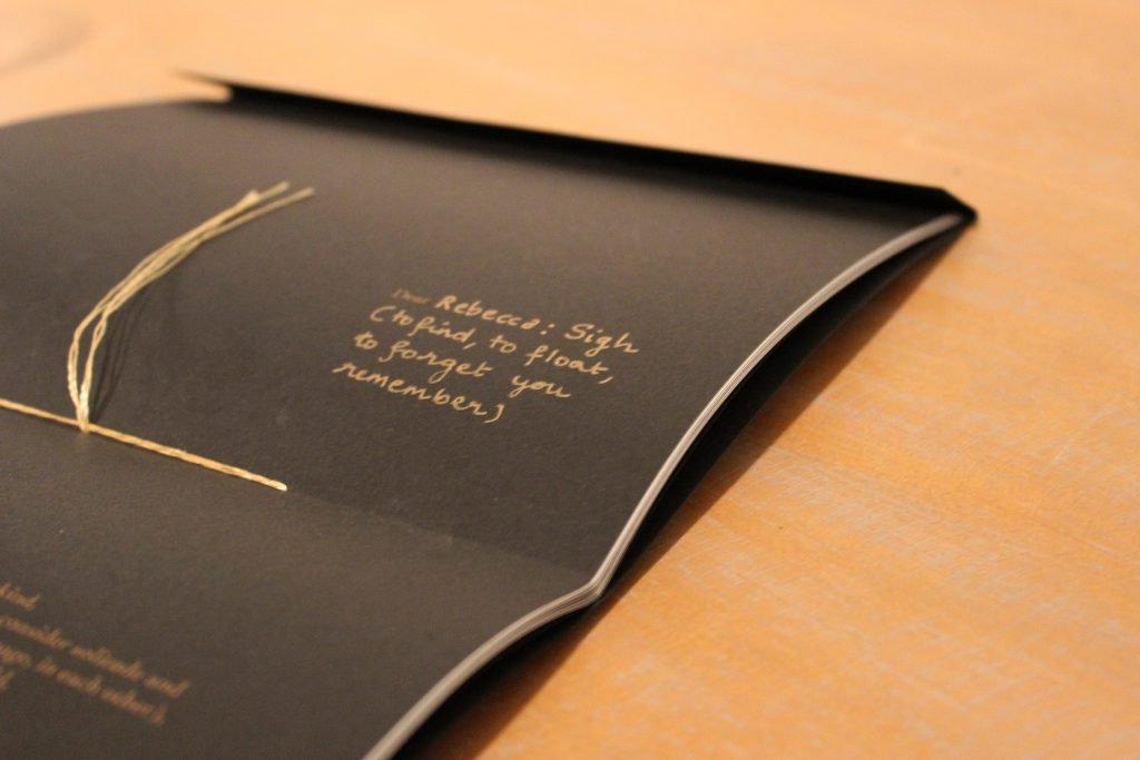 "Image: Udita Upadhyaya's book ""nevernotmusic"" (detail). On a wooden tabletop, the book lies open to the centerfold, showing black paper, gold thread, and gold writing. The word ""Dear"" is legible in gold type, followed by gold handwriting: ""Rebecca: Sign (to find, to float, to forget you remember)."" Photo by Caleb Neubauer."