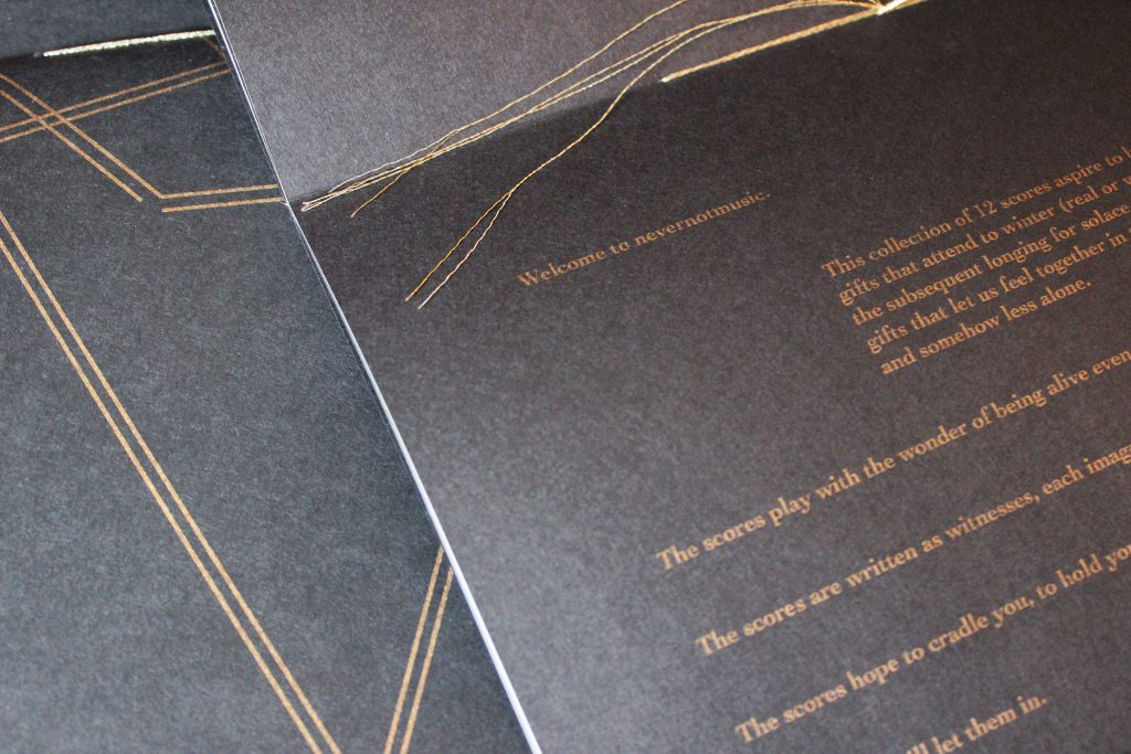 "Image: Udita Upadhyaya's book ""nevernotmusic"" (detail). The book lies open to the centerfold, showing black paper, gold thread, and gold type. Part of the lower page is visible, with the text beginning, ""Welcome to nevernotmusic,"" and including part of a description of the project of 12 scores and phrases like ""The scores play with the wonder of being alive even…"" and ""The scores are written as witnesses…."" Behind the open centerfold is part of the front cover of another copy. Photo by Caleb Neubauer."