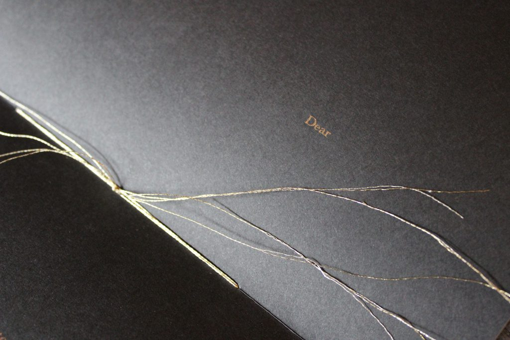 "Image: Udita Upadhyaya's book ""nevernotmusic"" (detail). The book lies open to the centerfold (in close-up), showing black paper, knotted gold thread (the book's stitching), and gold type (reading ""Dear""). Photo by Caleb Neubauer."