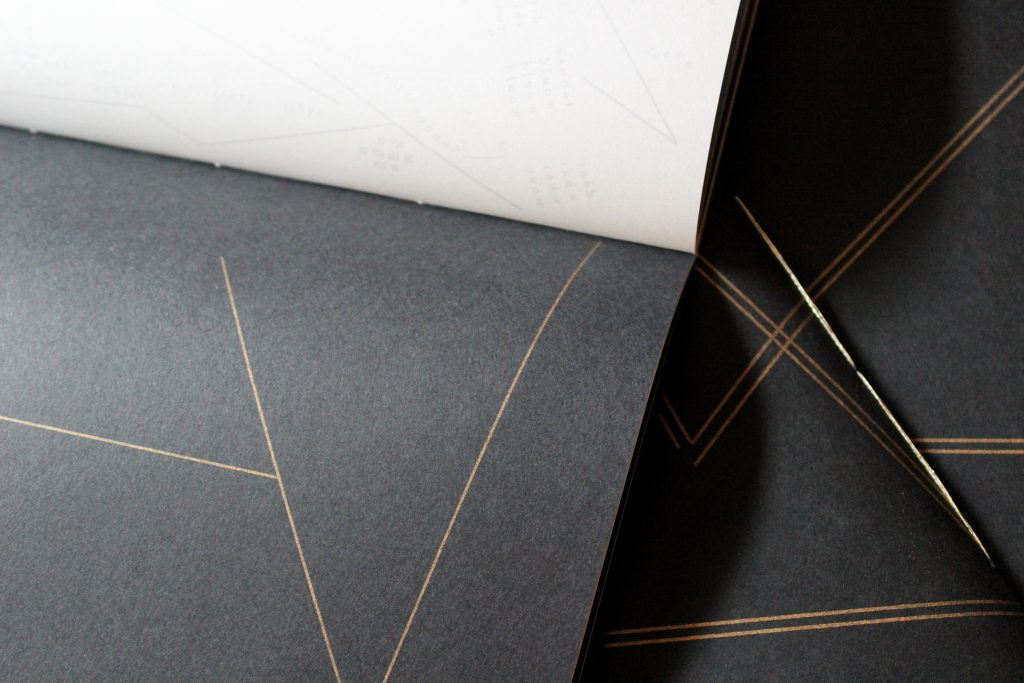 "Image: Udita Upadhyaya's book ""nevernotmusic"" (detail). Part of one page-spread is visible, with opaque black paper on one page (on which three thin gold lines touch to form large open triangles) and with whitish vellum on the other page (with lines, open triangles, and letters printed on the other side of the sheet of vellum, and slightly visible through it). In the background, beyond this copy, is part of the front cover of two other copies, with gold stitching and straight gold lines on black paper. Photo by Caleb Neubauer."