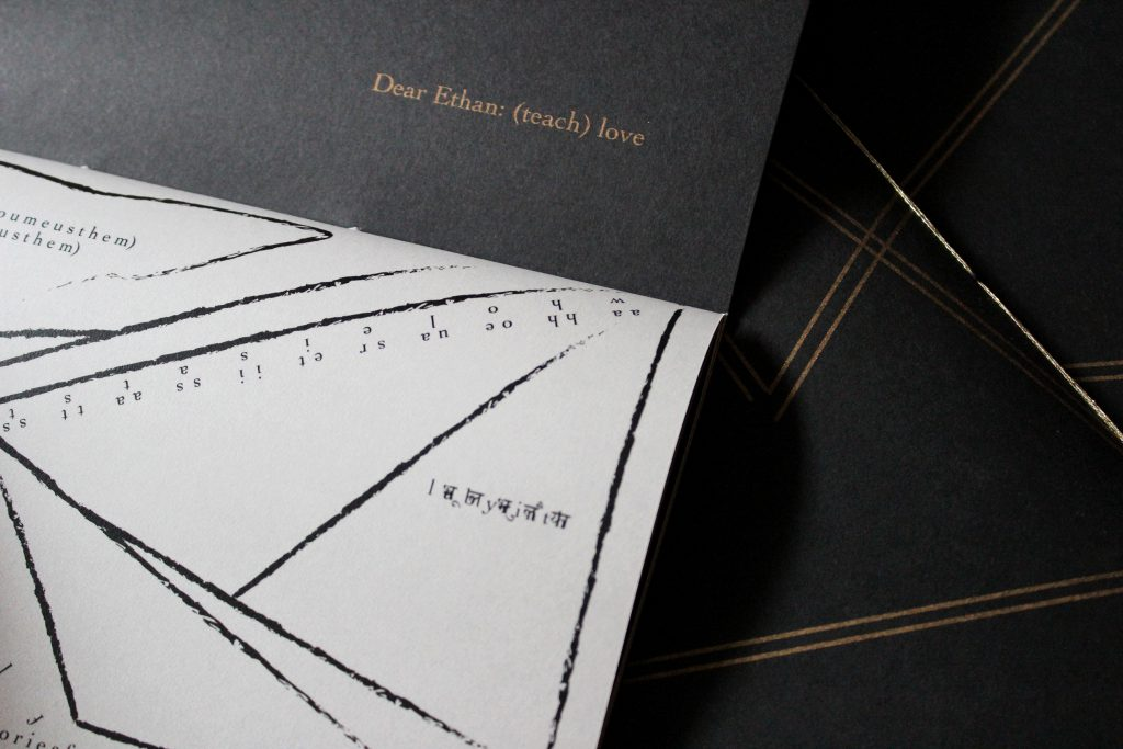 "Image: Udita Upadhyaya's book ""nevernotmusic"" (detail), showing part of the score, ""Dear Ethan: (teach) love."" Part of one page-spread is visible, with opaque black paper on the upper page (where the score's title appears in gold type) and with whitish vellum on the lower page (with gestural lines, triangles, and text in English and Hindi, printed in black ink). In the background, beyond this copy, is part of the front cover of two other copies, with gold stitching and straight gold lines on black paper. Photo by Caleb Neubauer."