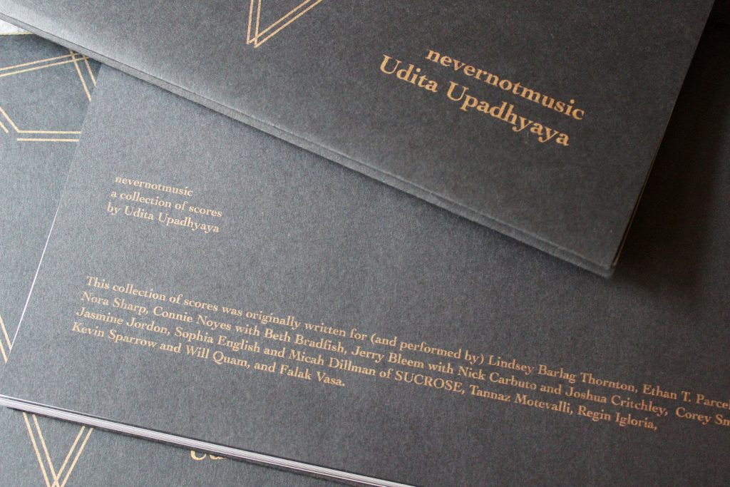 "Image: Udita Upadhyaya's book ""nevernotmusic"" (detail). Three copies are in a loose pile, showing parts of the front cover and of the back cover (beginning with ""nevernotmusic / a collection of scores / by Udita Upadhyaya"" and listing the performers for whom the scores were originally written). Text and motifs are in gold on black paper. Photo by Caleb Neubauer."