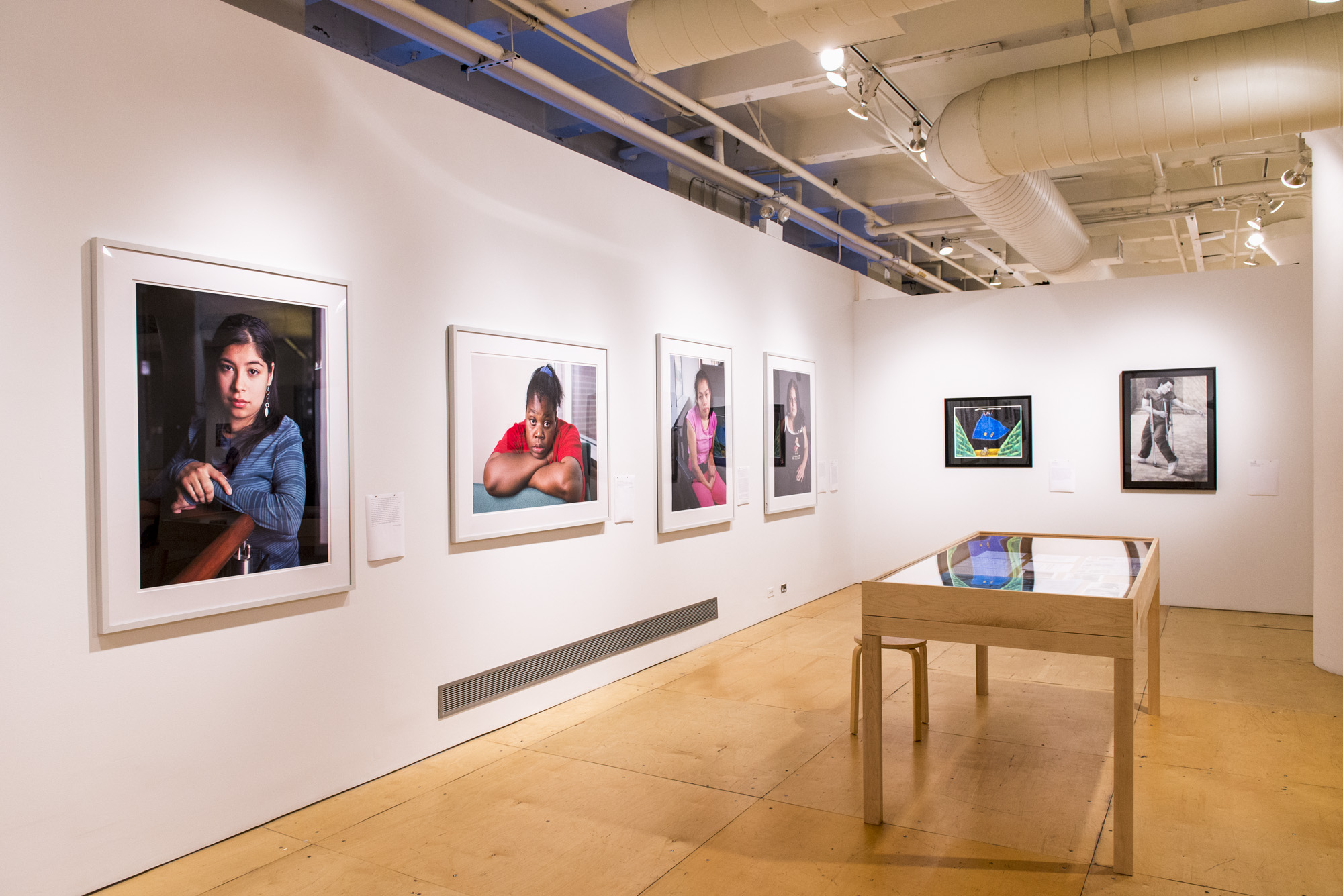 Image description: a view of two gallery walls featuring primarily large format photography portraits; to the right is a display table with printed ephemera. Photo by Ryan Edmund.