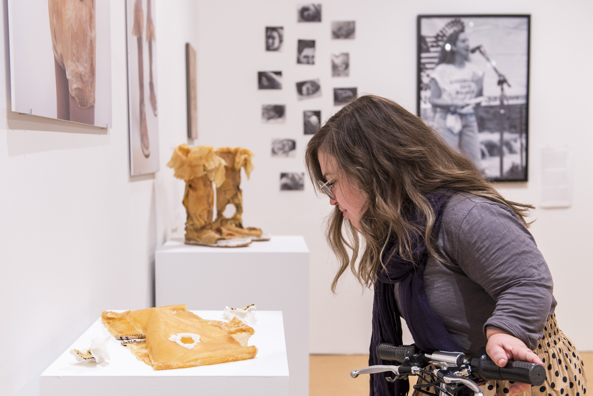 Image: Bri Beck leans into the frame from the right side, looking down at a tan mixed media garment piece on a white pedestal. Other works can be seen in the background. Photo by Ryan Edmund.
