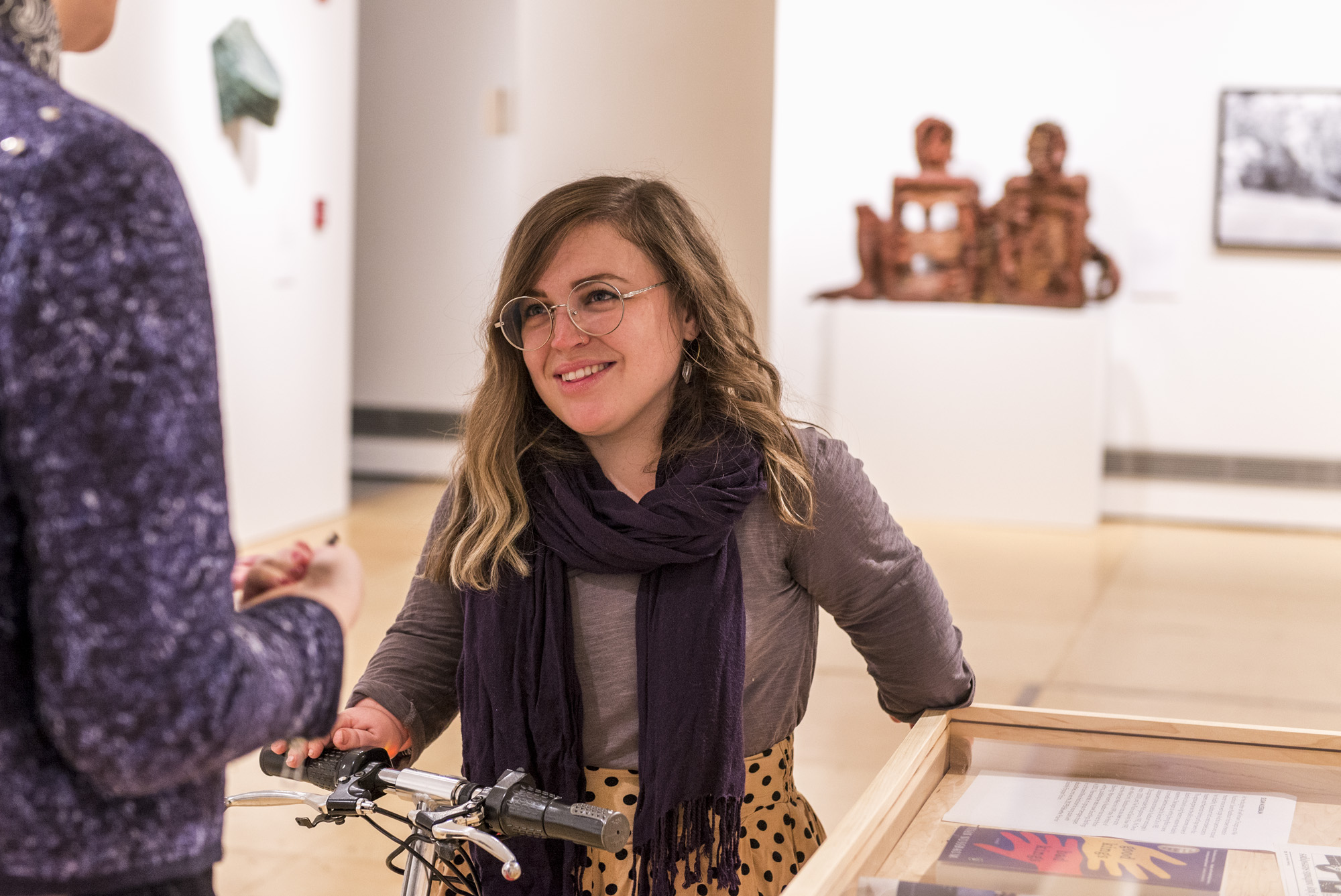 Image: Bri Beck seen in the galleries, wearing a grey sweater and dark scarf; the handlebars of her motorized scooter are visible; Courtney Graham's arm edges into the frame from the left as the two of them are in coversation. Photo by Ryan Edmund.