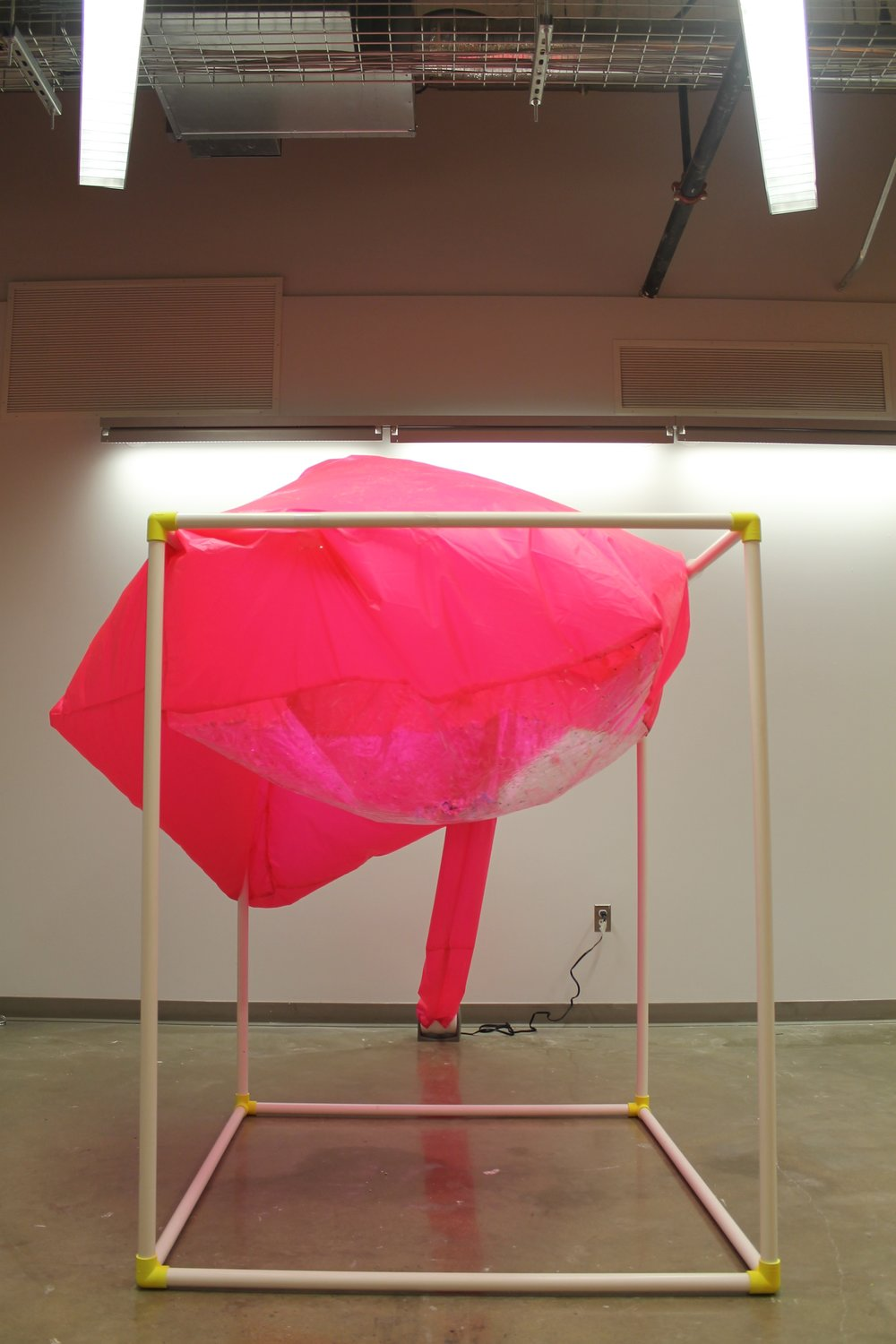 "Image: a large pink semi-inflated cube sits atop a white PVC structure; it droops to the left. ""Negotiating Space: Othered by Design"" by Bri Beck, courtesy of the artist."