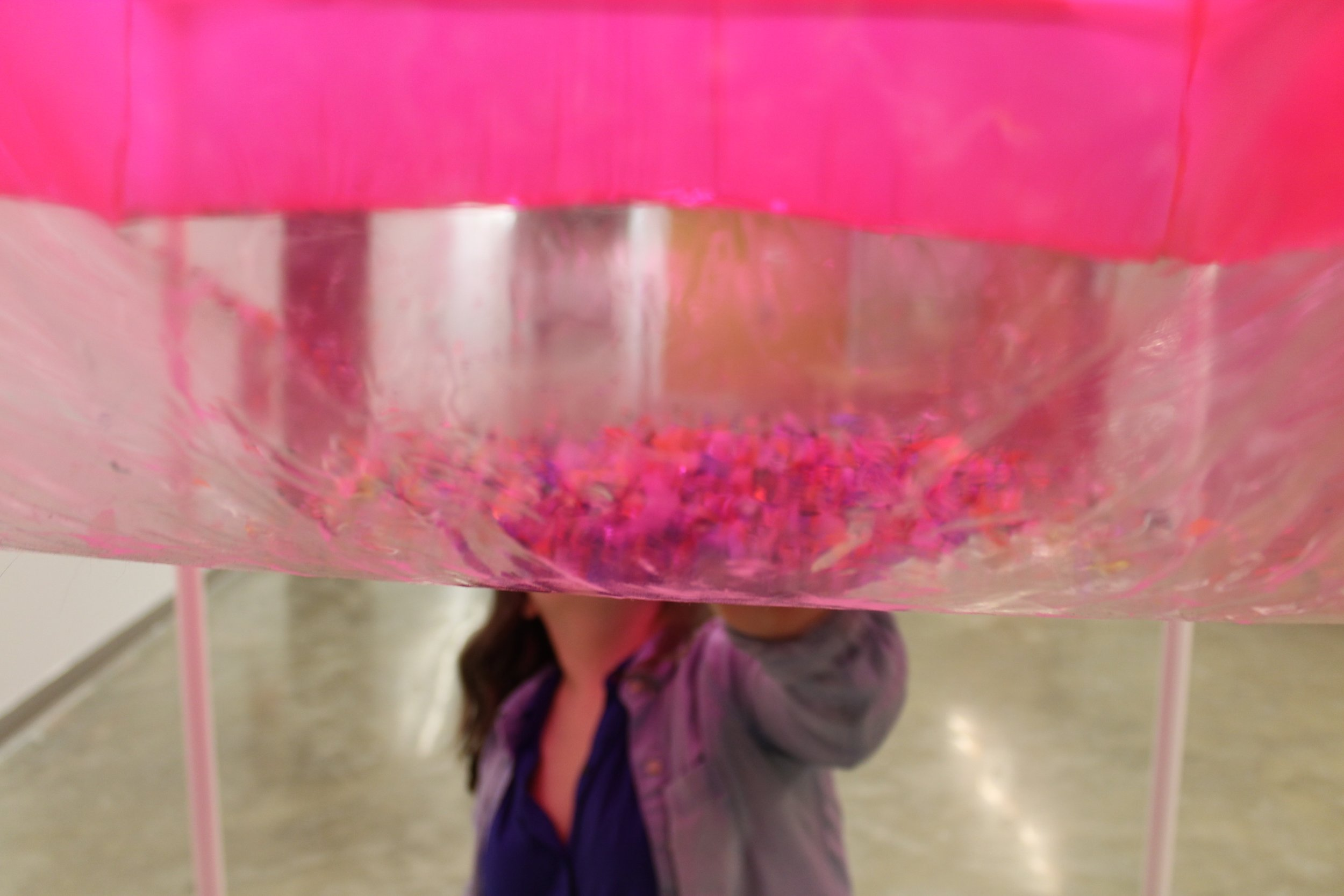 """Image: a large pink inflated cube fills the top half of the frame, it is semi-transparent and confetti is seen inside; Bri Beck is on the other side of the work, touching it with her hand, her face is not visible. """"Negotiating Space: Othered by Design"""" by Bri Beck, courtesy of the artist."""