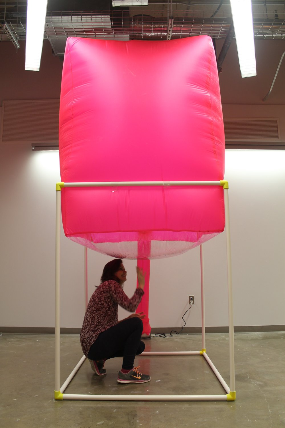 "Image: a large pink inflated cube sits atop a white PVC structure with a person crouched beneath it. ""Negotiating Space: Othered by Design"" by Bri Beck, courtesy of the artist."