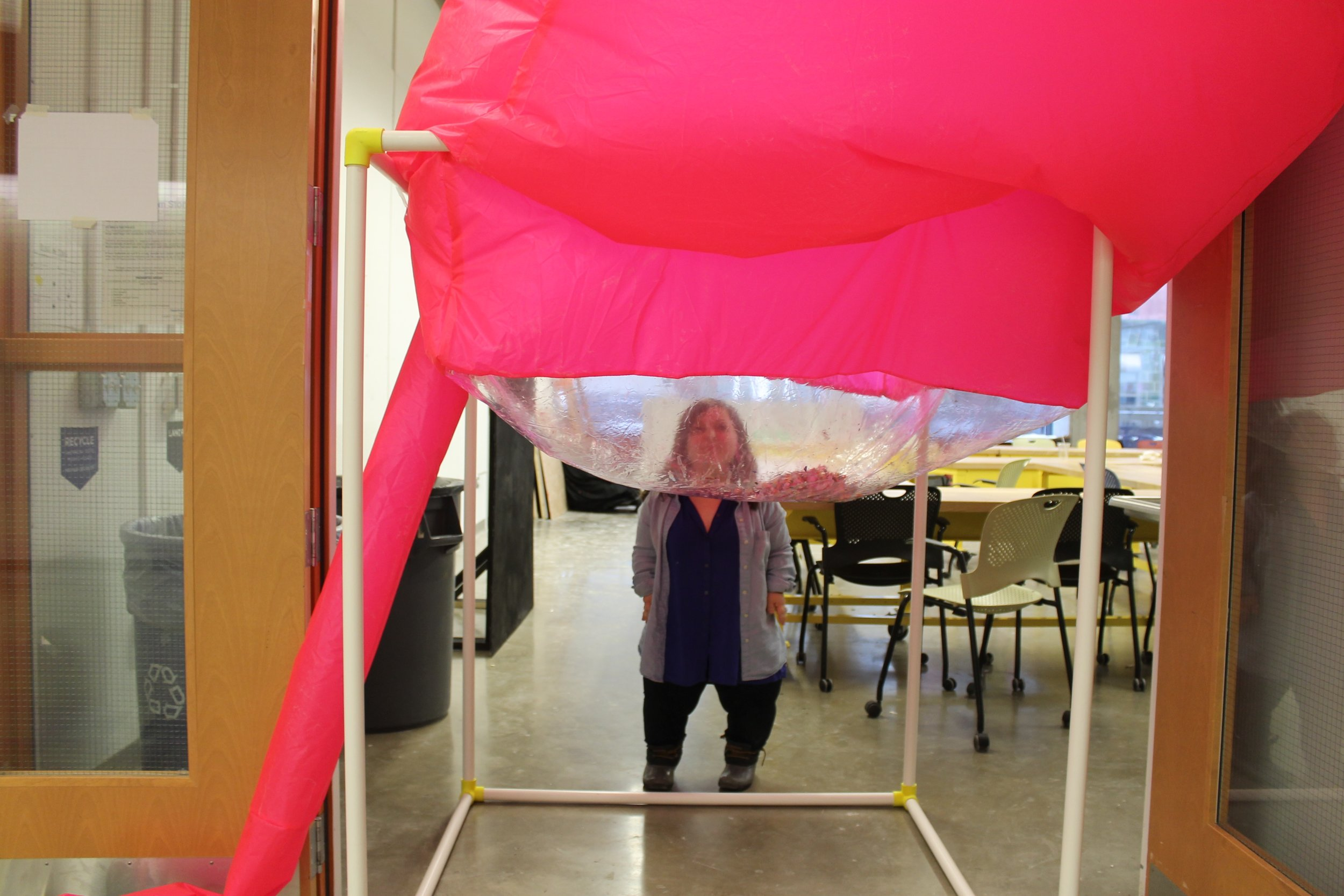 "Image: a large pink inflated cube sits atop a white PVC structure; it is positioned in a doorway and Bri Beck is standing on the far side of it, semi-visible. ""Negotiating Space: Othered by Design"" by Bri Beck, courtesy of the artist."