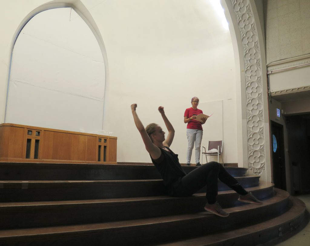 Image: Maxine Patronik and Lani T. Montreal rehearse for their Body Passages piece at the Chicago Danztheatre Ensemble Auditorium. Lani stands on-stage in the background, reading from an open folder. Maxine sits on one of the stage's steps in the foreground, leaning back with fists and bent arms raised above her head and with her feet on the step below. Lani wears a red t-shirt and light jeans. Maxine wears a black tank-top and black pants. The stairs are brown and curved, the proscenium arch is white and patterned, and the the stage walls and a large window covering are white. A long wooden altarpiece with crosses is positioned along the stage's back wall. Photo by Marya Spont-Lemus.
