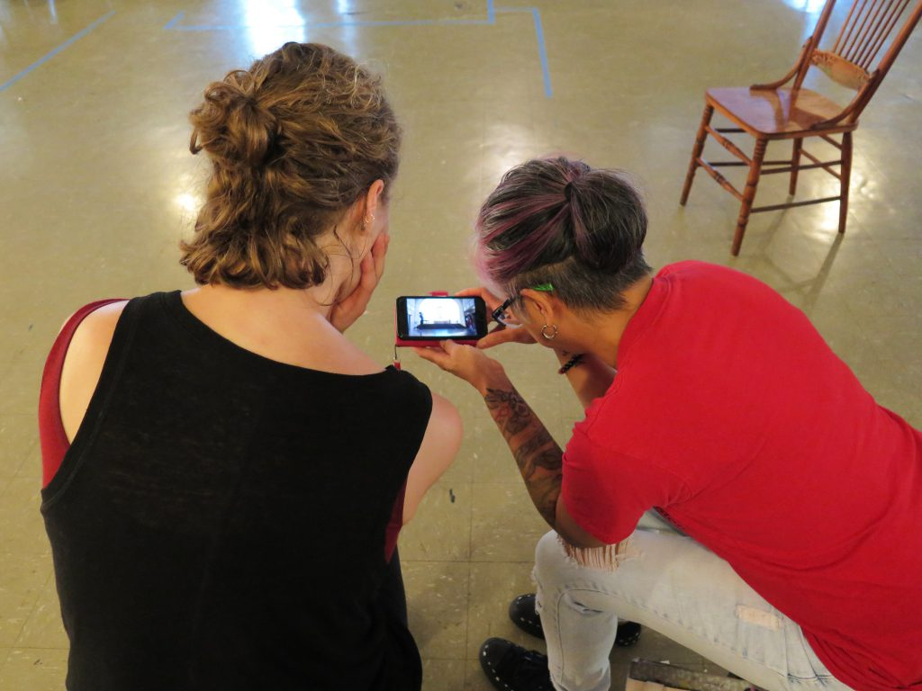 Image: Maxine Patronik and Lani T. Montreal at a rehearsal at Chicago Danztheatre. The artists sit side-by-side in chairs, backs toward the camera. Lani holds a camera-phone between them as they watch its bright screen, which shows a recording of themselves performing in the same space. Lani wears a red t-shirt and light jeans. Maxine wears a black tank-top with a maroon strap beneath. The auditorium's floor and a chair are in the background. Photo by Marya Spont-Lemus.