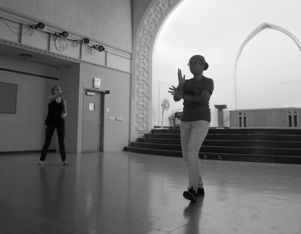 Image: Maxine Patronik and Lani T. Montreal rehearse for their Body Passages piece at the Chicago Danztheatre Ensemble Auditorium. In this black-and-white image, Maxine and Lani stand upright on the floor in front of the stage, roughly perpendicular to each other and both facing diagonally past the camera. In the foreground, Lani raises her arms in front of her chest, perpendicular to each other and with palms open, and leans on her back foot. In the background, Maxine lifts one arm straight ahead of her and holds the other by her abdomen. Lani wears a dark t-shirt and light jeans. Maxine wears a dark tank-top and dark pants. Photo by Marya Spont-Lemus.