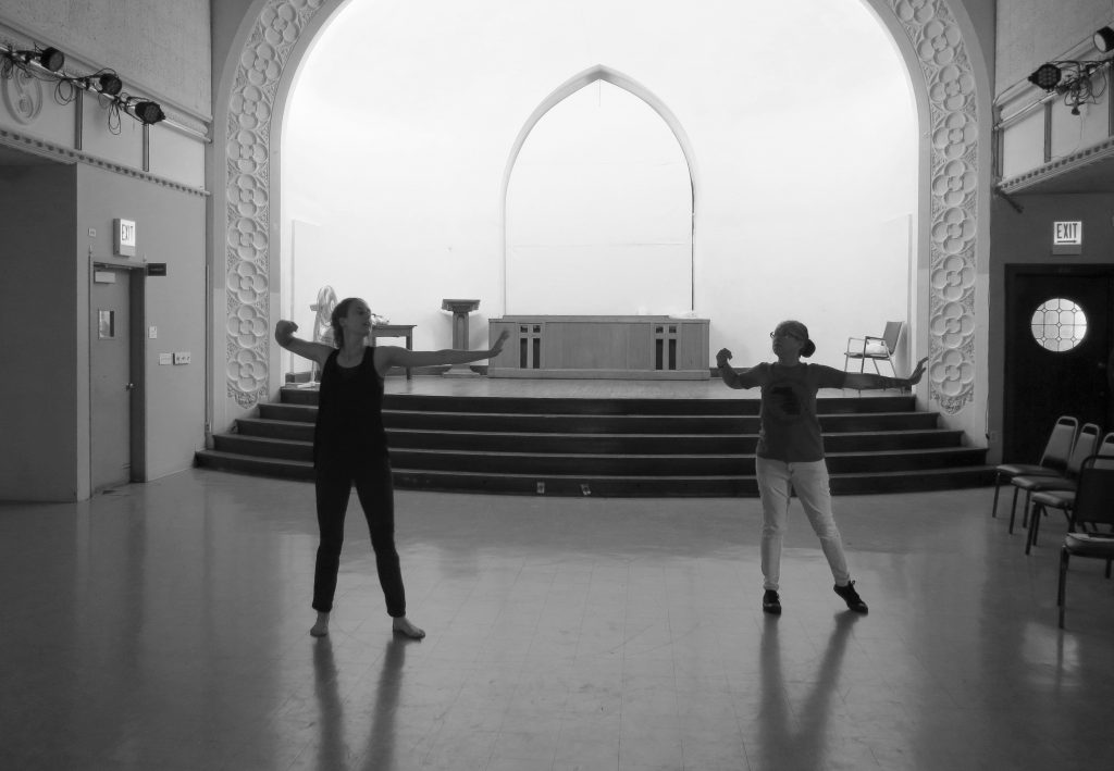 Image: Maxine Patronik and Lani T. Montreal rehearse for their Body Passages piece at the Chicago Danztheatre Ensemble Auditorium. In this black-and-white image, both artists stand dark in the middle of the floor, with the stage bright in the background. Maxine's and Lani's bodies face the camera, as the artists face each other. They strike a similar pose — feet spread shoulder-width apart, left arms stretching to their left sides, left wrists cocked, and right arms bent to their right sides. Lani wears a dark t-shirt, light jeans, and shoes. Maxine wears a dark tank-top and dark pants and is barefoot. Photo by Marya Spont-Lemus.