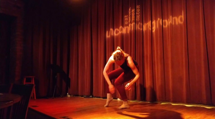 """Image: Maxine Patronik performs at a Body Passages event at Uncommon Ground. Maxine dances barefoot on a wooden stage, with """"uncommonground"""" projected on the maroon curtain behind her. She leans forward, with her body bent at the hips, knees, and elbows. She wears a dark top and maroon leggings. Photo courtesy of the artist."""