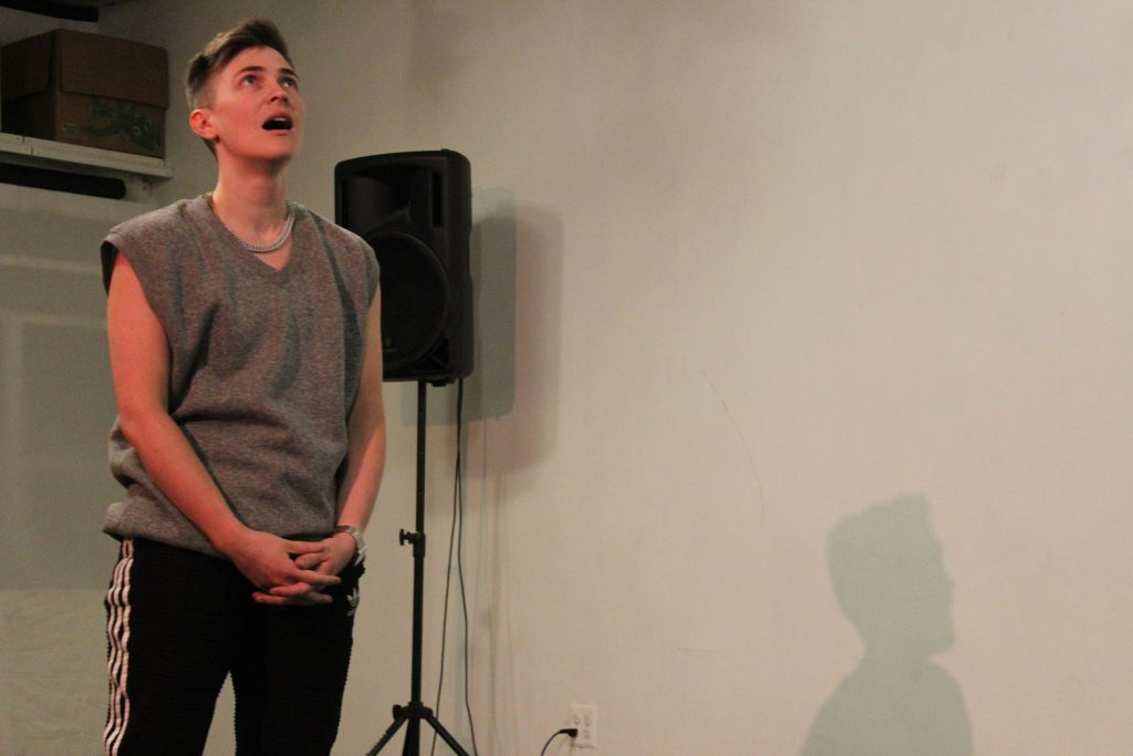 "Image: Nora Sharp performs in response to the score ""Dear Aron: (Destroy) Armor."" On the left side of the image, the performer stands with hands folded, looking up at the ceiling and singing. On the right side, part of Nora's shadow is visible, cast on the wall. The artist wears a grey sleeveless shirt and black athletic pants with white stripes. Photo by Caleb Neubauer."