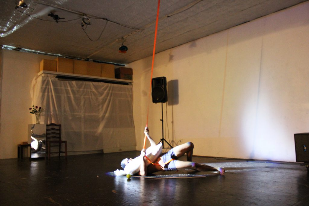 "Image: Regin Igloria performs in response to the score ""Dear Regin: SOAK (in silence)."" Regin lies on the floor of TriTriangle, lit by a spotlight. Regin is barefoot and wears a swim cap, goggles, and spandex shorts. A sandbag lies across Regin's chest. The artist reaches his arms around the sandbag to grip an orange strap that hangs from the ceiling, as he pushes his hips off the floor. Photo by Caleb Neubauer."