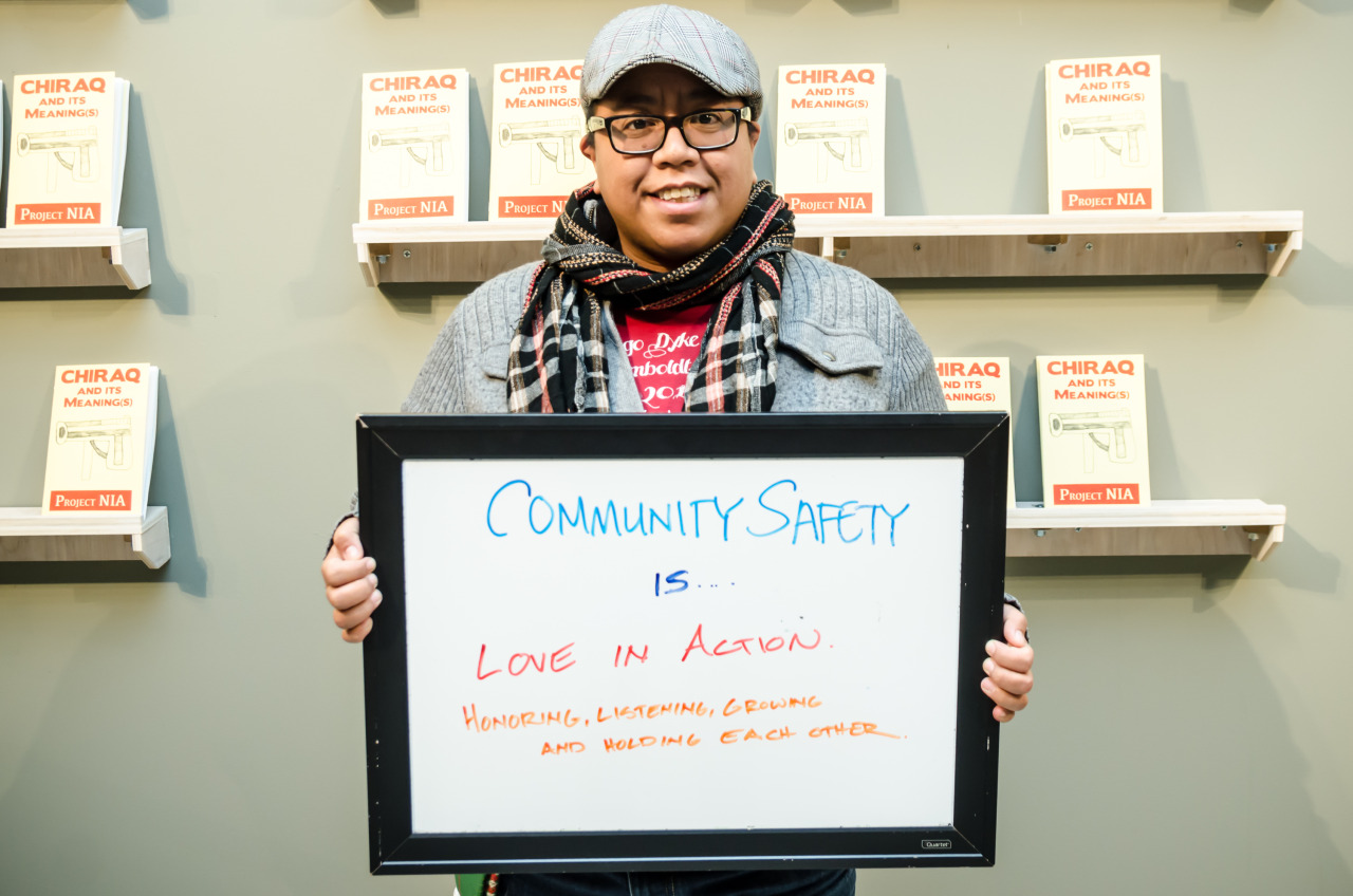 "Image: A person of color stands in front of a wall with shelves that have pamphlets with the words ""CHIRAQ And Its Meaning(s)"" by Project NIA. This person holds a dry-erase board with ""Community Safety Is… Love in Action. Honoring, Listening, Growing, and Holding Each Other."" in the center. Photo courtesy of the artist."