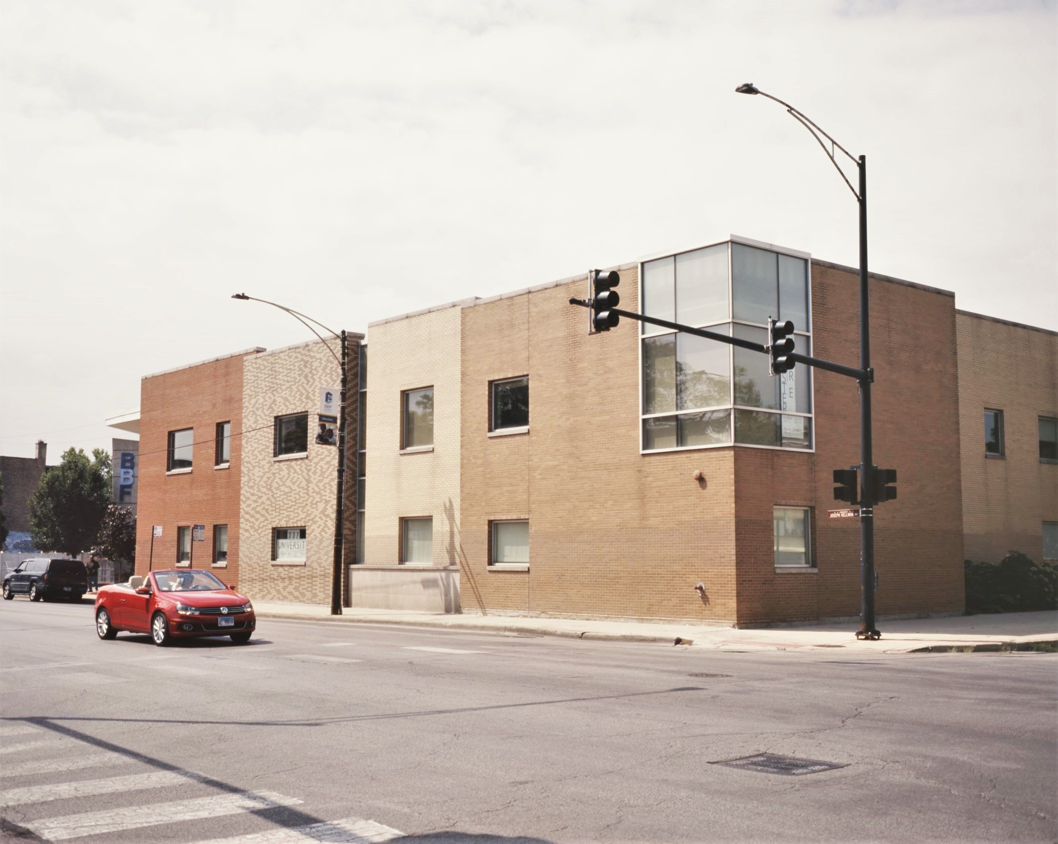 Image: The BBF Family Services Center, seen on a sunny day from the NE corner of 15th and Pulaski in North Lawndale. Designed by architect Lucien Lagrange, the building's long, two-story play-block facade varies in dimension and brick pattern from end to end. A red Volkswagen cabriolet with the top down is stopped momentarily at the light in front of the building. Photo by Eric K. Roberts.