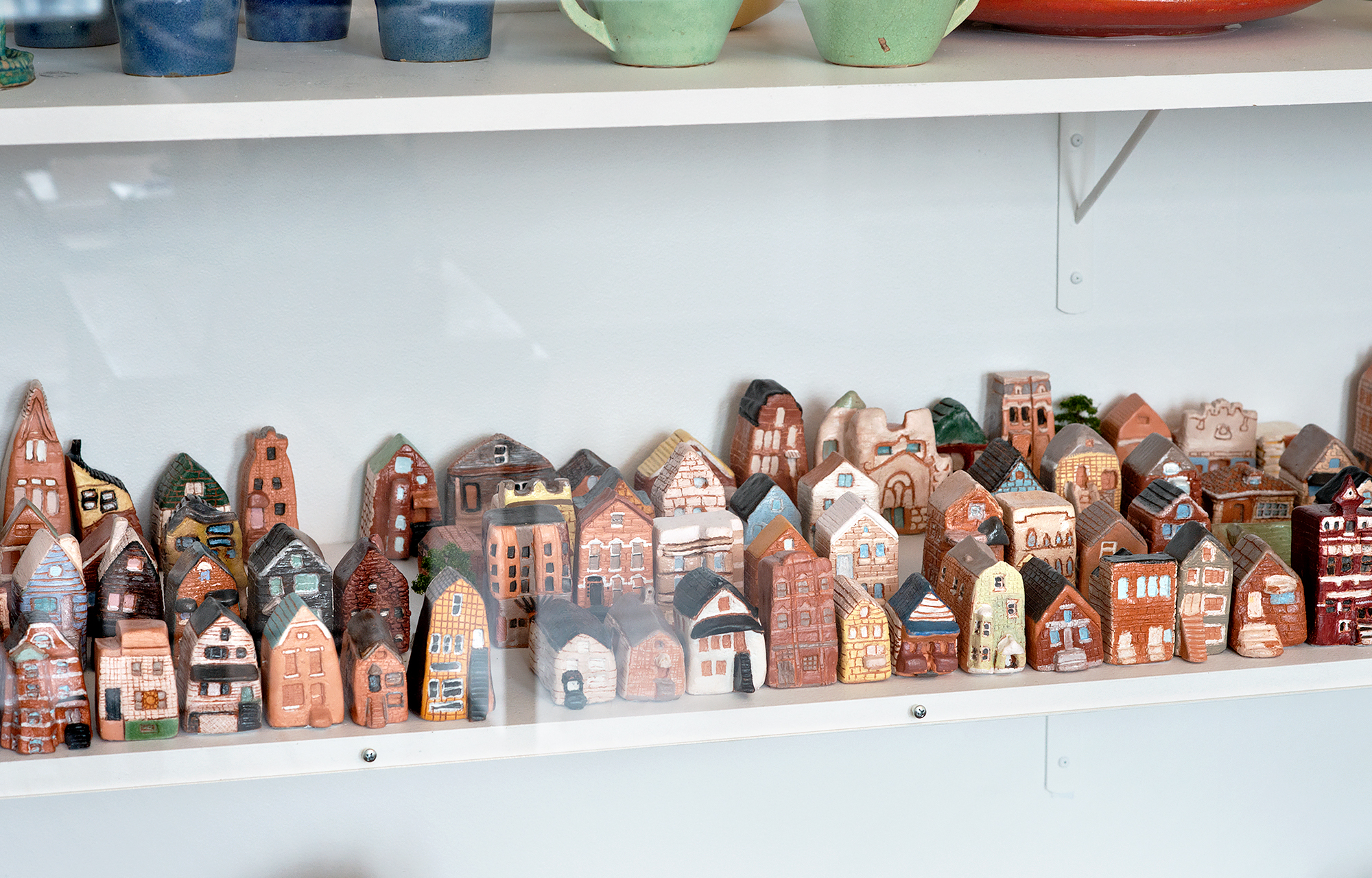 Image: Detail view of ceramic houses and stores made by Nicole Marroquin's students at Benito Juarez Community Academy High School, as seen in a display case at Hull House. The small ceramics reflect a range of different building styles, from brick to colorful siding, and single-family homes to apartment complexes. They are arranged in dense grids similar to the layout of Chicago neighborhoods. Photo by Greg Ruffing.
