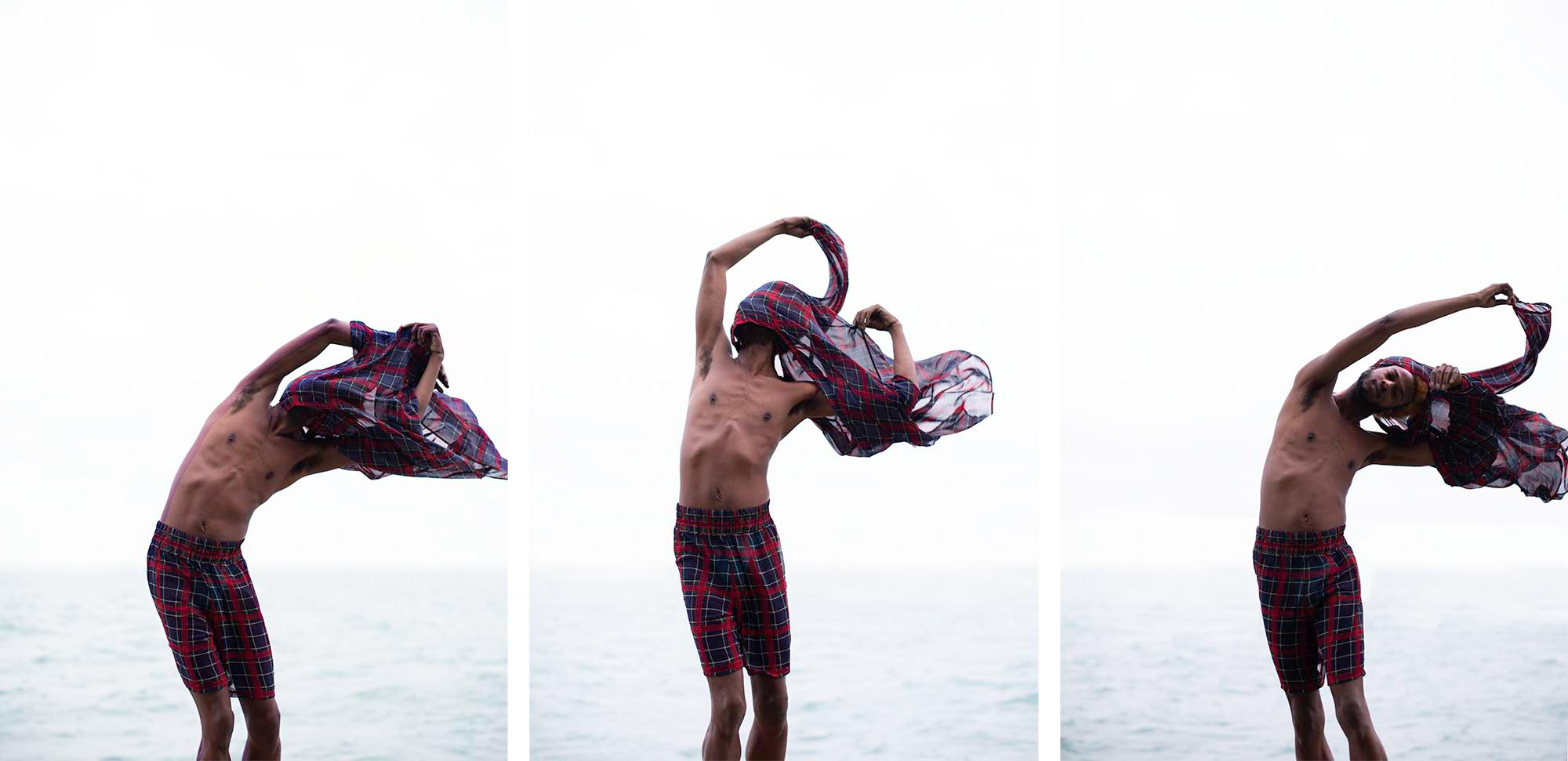 Image: A triptych of Wallace standing in front of a body of water, taking of a sheer plaid shirt. Each image shows Wallace with the shirt over his head, in different postures, and points of disrobing as the shirt waves in the wind. Photo by Chelsea Ross