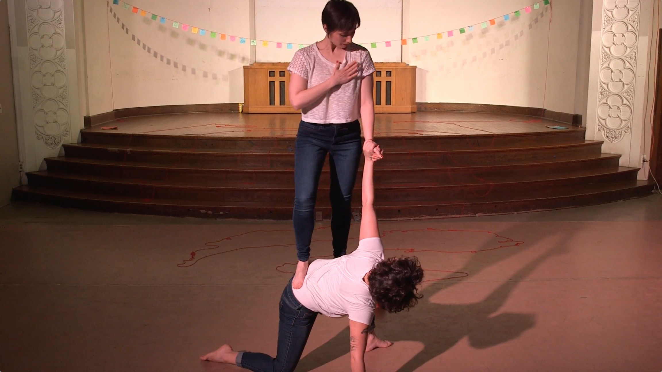 "Featured image: Maggie Robinson and Allison Sokolowski performing in ""I Am"" at the Chicago Danztheatre Auditorium, as part of the Body Passages culminating event. Maggie balances with one foot, knee, and hand on the floor, as Allison stands on Maggie's lower back. The performers hold each other's left hands and look at each other. Both are barefoot and wear white t-shirts and jeans. Behind them is a well-lit stage, with a string of colorful paper suspended across it. Still from a video by John Borowski."