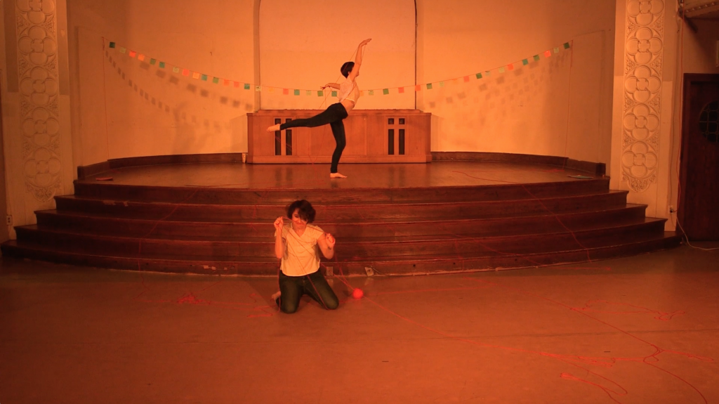 "Image: Maggie Robinson and Allison Sokolowski performing in ""I Am."" In the foreground, Maggie kneels on the floor, holding up strands of red yarn, which is also strewn across the floor. In the background, Allison stands onstage in an arabesque, also holding up red yarn. Both performers are barefoot and wear white t-shirts and jeans. The stage is bathed in warm orange light and has a string of colorful paper suspended across it. Still from a video by John Borowski."